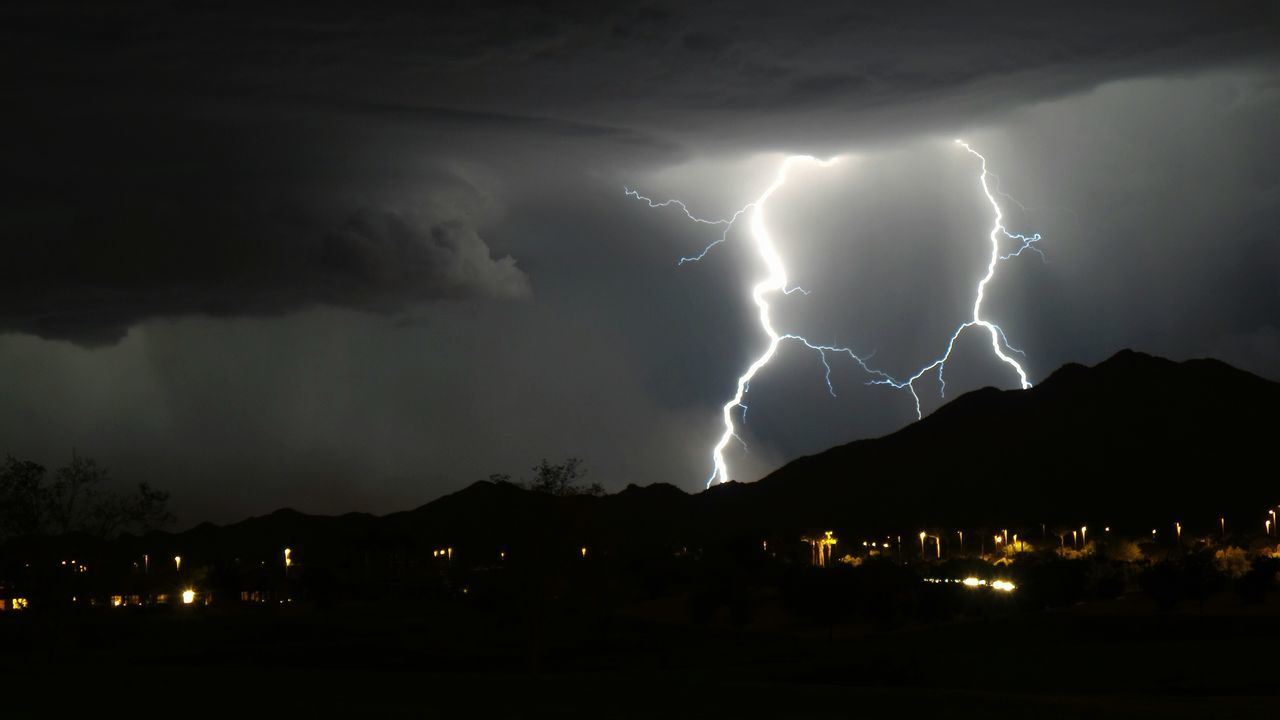 lightning, power in nature, night, forked lightning, thunderstorm, illuminated, weather, danger, storm cloud, sky, storm, dramatic sky, mountain, cloud - sky, nature, electricity, beauty in nature, scenics, silhouette, no people, outdoors, built structure, cityscape, building exterior, architecture, city