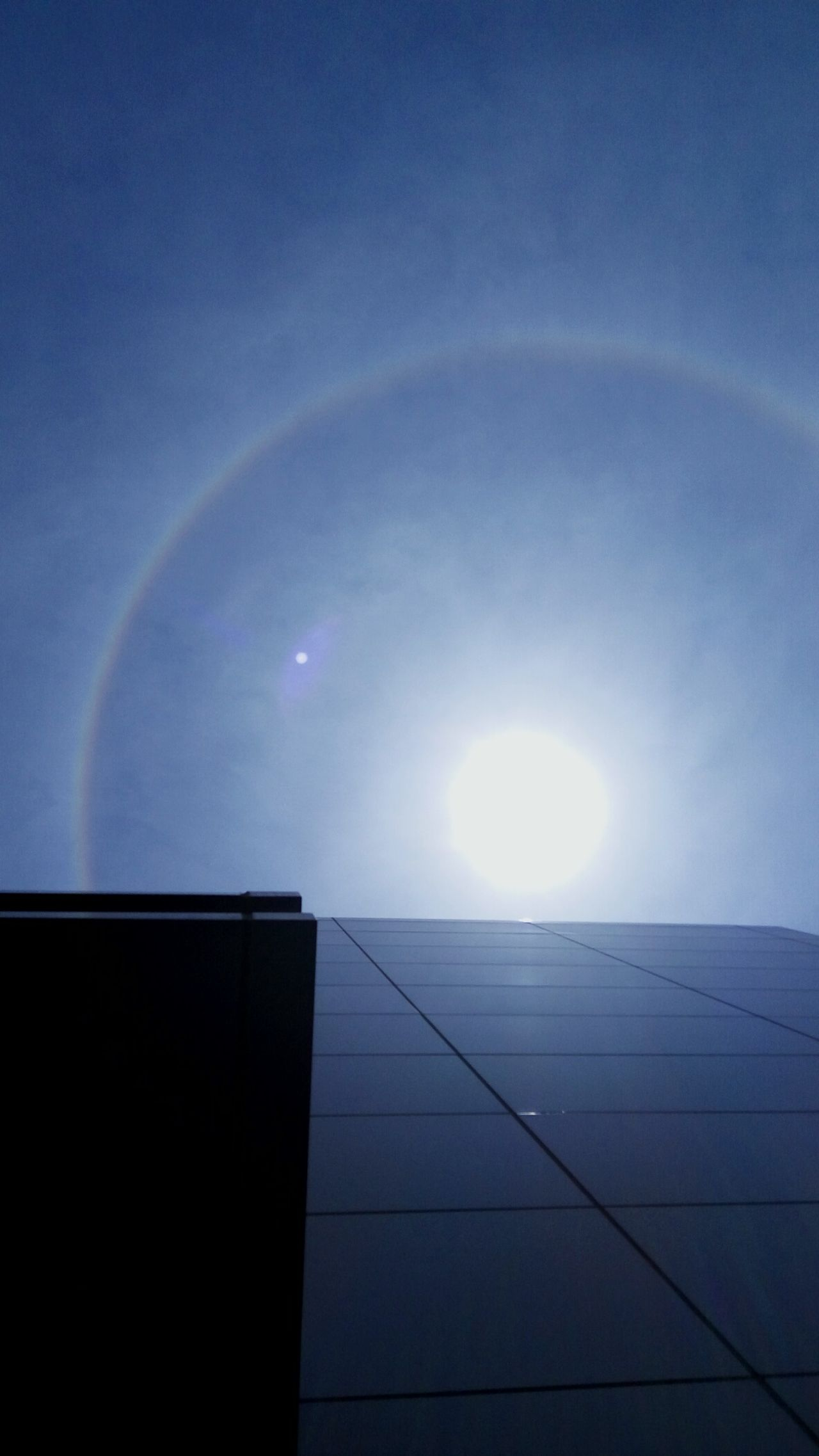 This is Halo Phenomenon that happened today in my workplace. I notice it once I saw a few person took some photos and video of the Sun's 'son' . The son appearance is due to the crystallization occurred at the troposphere and act as the mirror, reflects the Sun image.