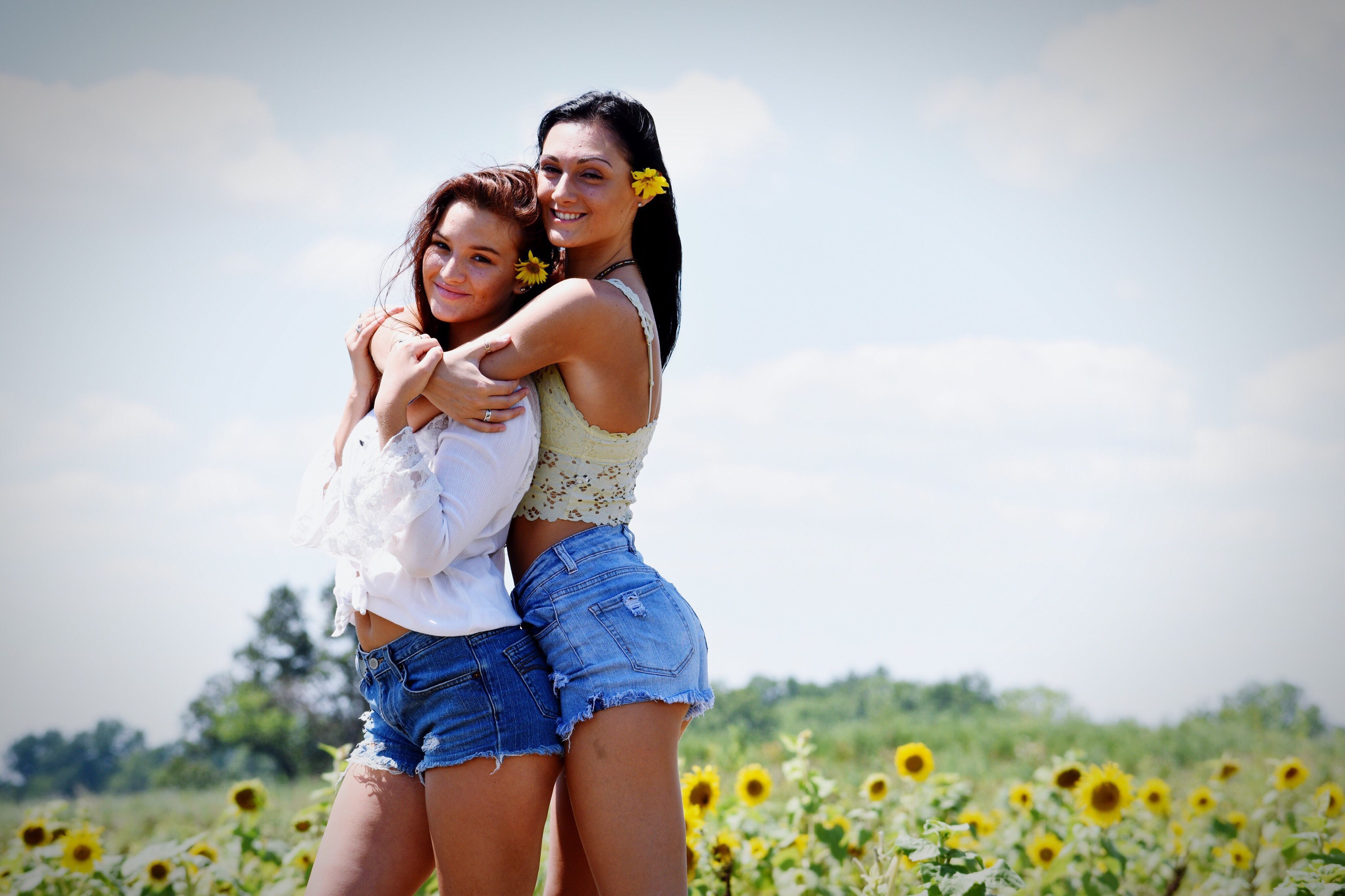 three quarter length, sky, leisure activity, real people, young women, young adult, togetherness, casual clothing, nature, lifestyles, hot pants, shorts, two people, love, standing, happiness, outdoors, beauty in nature, field, cloud - sky, day, landscape, front view, smiling, bonding, grass, vacations, piggyback, beautiful woman