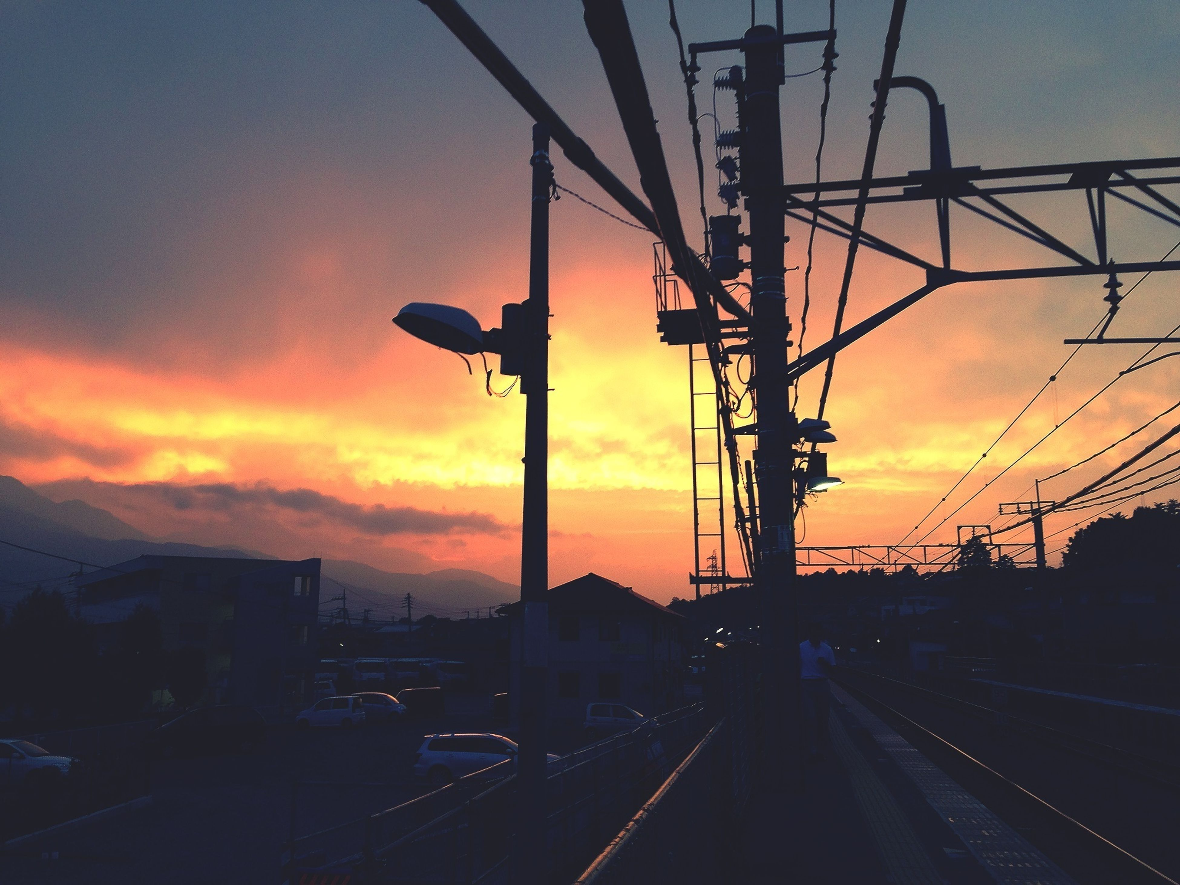 sunset, transportation, sky, orange color, silhouette, cloud - sky, car, railroad track, road, land vehicle, street light, dusk, electricity pylon, power line, mode of transport, connection, built structure, dramatic sky, architecture, street