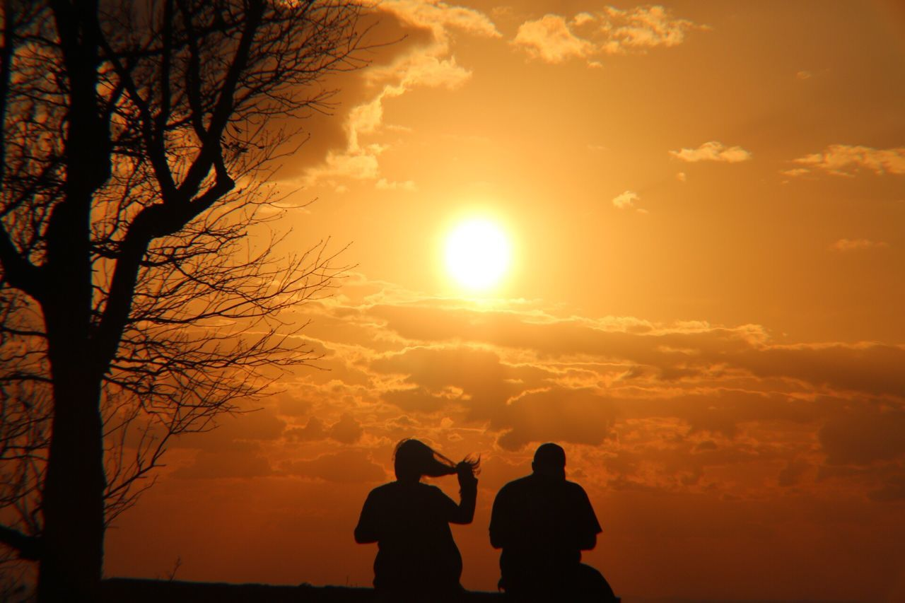 sunset, silhouette, sun, real people, orange color, two people, nature, sky, beauty in nature, men, togetherness, scenics, leisure activity, sunlight, tree, tranquility, outdoors, lifestyles, women, bonding, bare tree, people