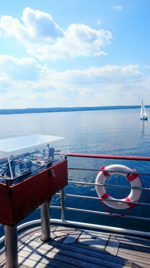 On A Boat Ship On The Sea On The Lake Control Board Sailing Boat Blue Skies Summer Day Ammersee Lifebelt Water Clouds And Sky Let's Go. Together.