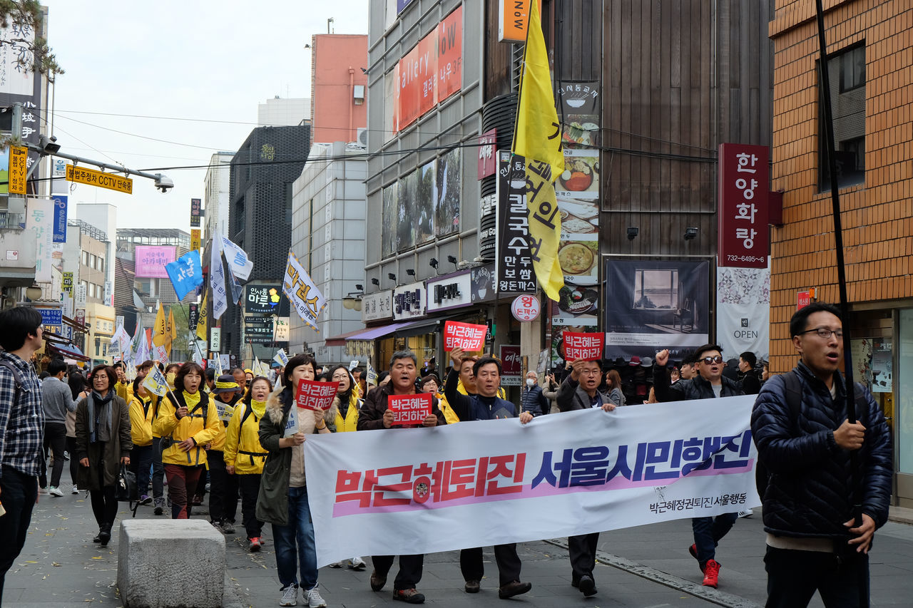 A group of Korean Presidential Protesters at a Seoul shopping street. Architecture Banner - Sign Building Exterior Built Structure City City Life Communication Crowd Day Korea Large Group Of People Men Outdoors People Placard Protest Protesters Protestor Real People Riot Road Street Text Women The Photojournalist - 2017 EyeEm Awards