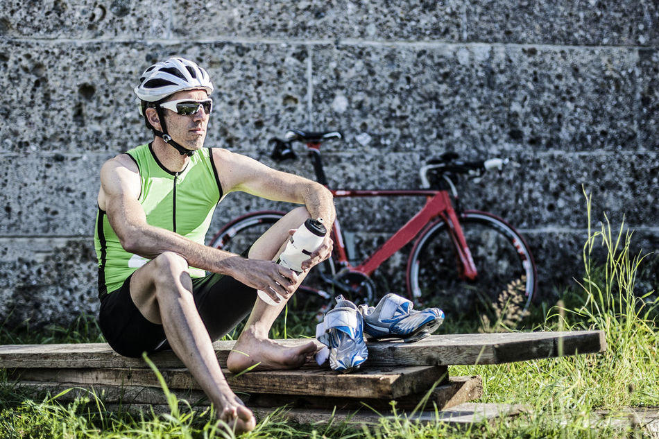 Portrait of triathlete recovering after the race 40 Adult Athlete Bicycle Bike Challenge Competition Cycling Man Nutrition Outdoors Portrait Race Recovering Recreation  Resting Roadbike Sitting Sports Sportsman Take A Rest Training Triathlete TRIATHLON Unfiltered