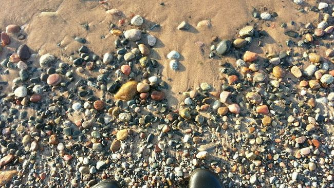 Smooth stones meeting wet sand under soft evening light. Textures And Surfaces Texture Smooth Stones Lake Superior Michigan Michigan Summer Michigan Beaches Point Iroquois Sunlight Evening Sun Colorful Stones Relaxing Slow Living Slow Life Beach Surfaces Beach Textures Looking Down Perspective Surface Image