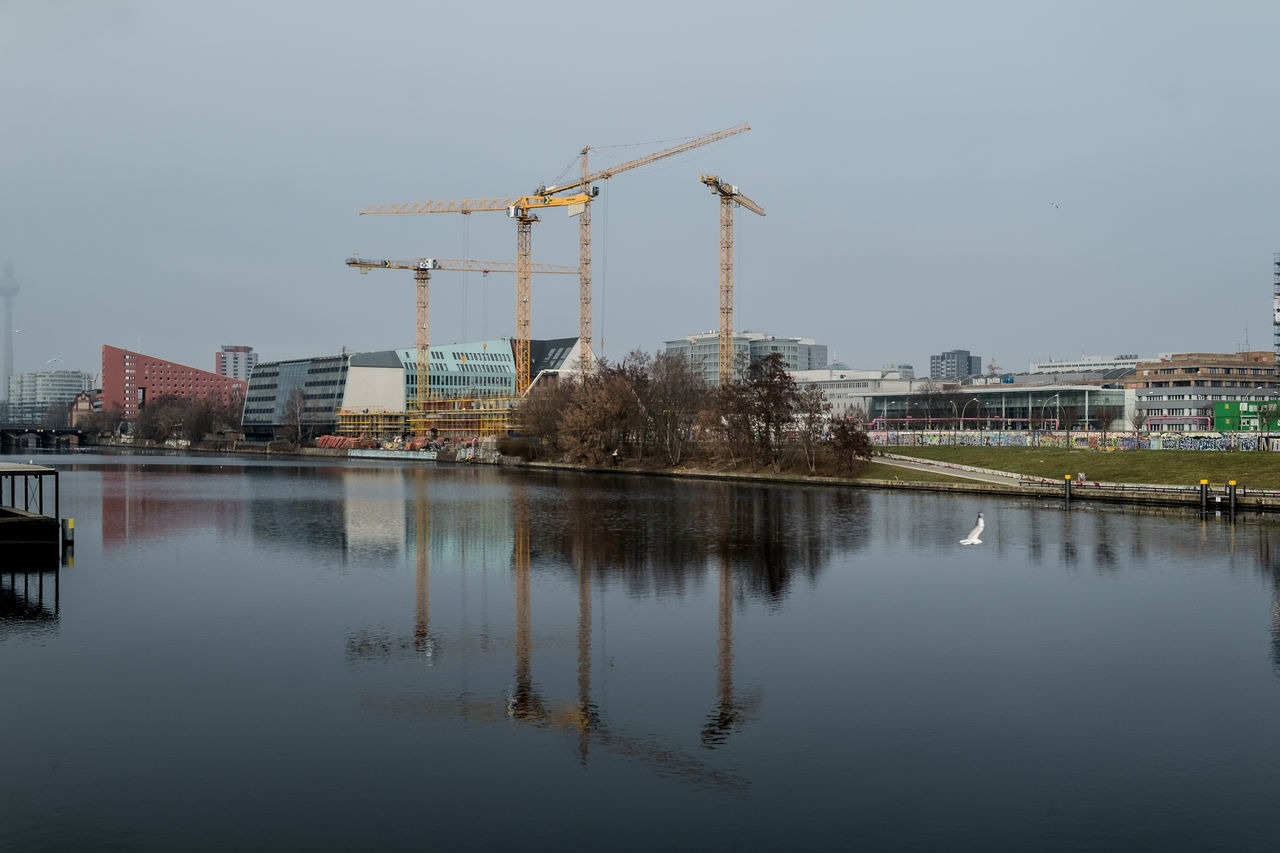 Architecture Berlin Building Exterior Built Structure City Construction Construction Machinery Construction Site Crane Crane - Construction Machinery Day Development Industry No People Outdoors Reflection Sky Spree Spree River Water