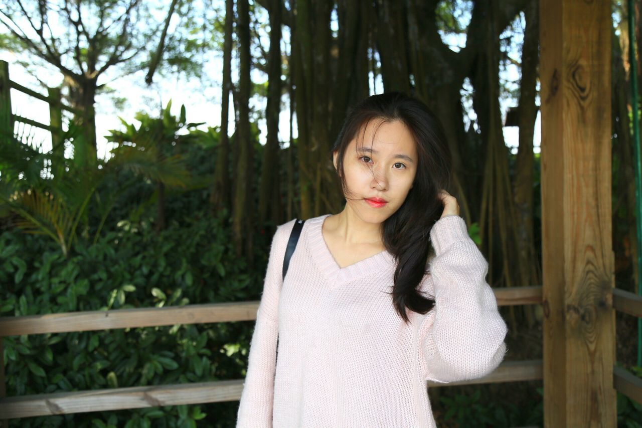 looking at camera, front view, one person, tree, portrait, waist up, standing, black hair, brown hair, casual clothing, young adult, long hair, day, beautiful woman, outdoors, real people, one young woman only, one woman only, young women, people, adults only, only women, adult, nature