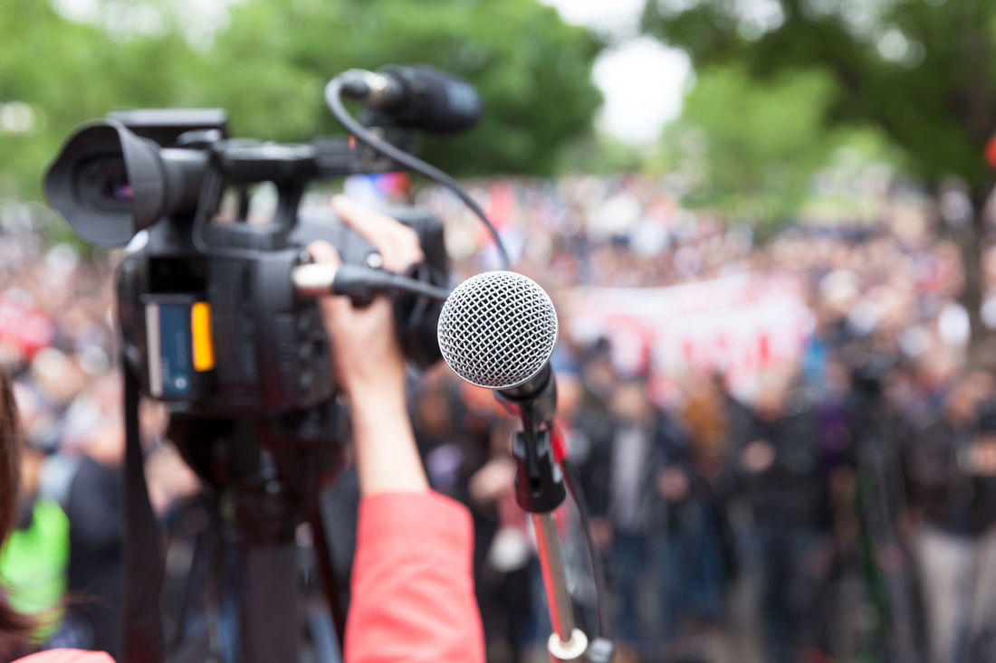 Microphone in focus against blurred crowd. Filming protest. Event Filming Meeting Politics Protest Audience Campaign Convention Crowd Demonstration Demonstrations  Election Group Mass Media Microphone People Political Presentation Protesters Rally Speaker Video Camera
