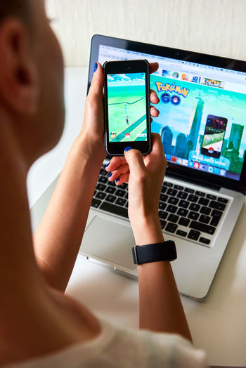 Riga, Latvia- July 17, 2016 : Woman playing a Pokemon Go game, home page of a game on a monitor screen on a background. Pokemon Go is a popular virtual reality game for mobile devices. The game allows players to capture, battle, and train virtual creatures, called Pokemon, who appear on device screens as though in the real world. App Application Close-up Communication Computer Monitor Editorial  Game Gaming Home Page Illustrative Illustrative Editorial Internet Laptop Monitor Network Play Pokemon Go Popular Reality Technology Wireless Technology Woman