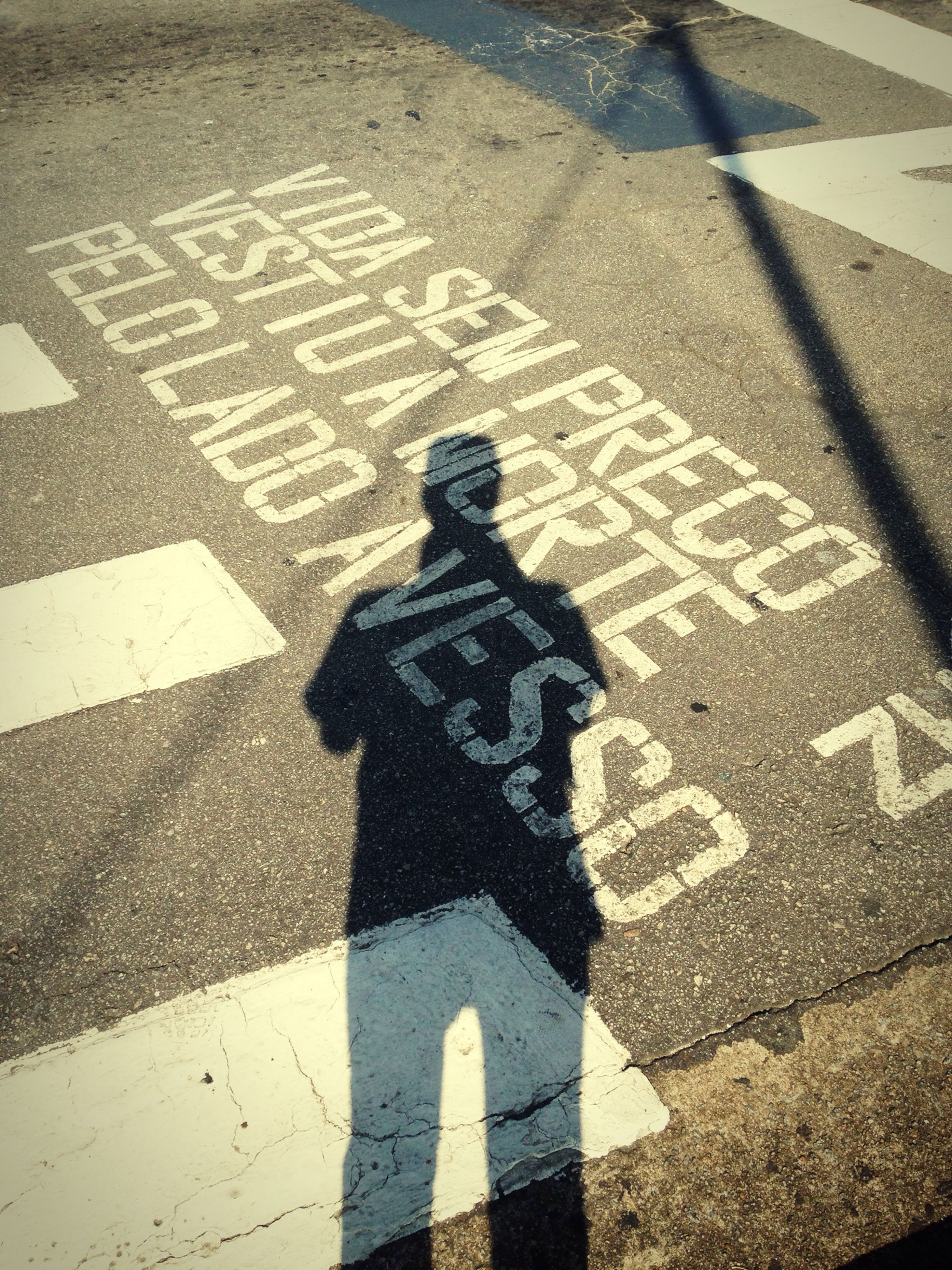 high angle view, shadow, street, road marking, focus on shadow, standing, road, sunlight, lifestyles, asphalt, men, communication, unrecognizable person, leisure activity, day, human representation, low section, text