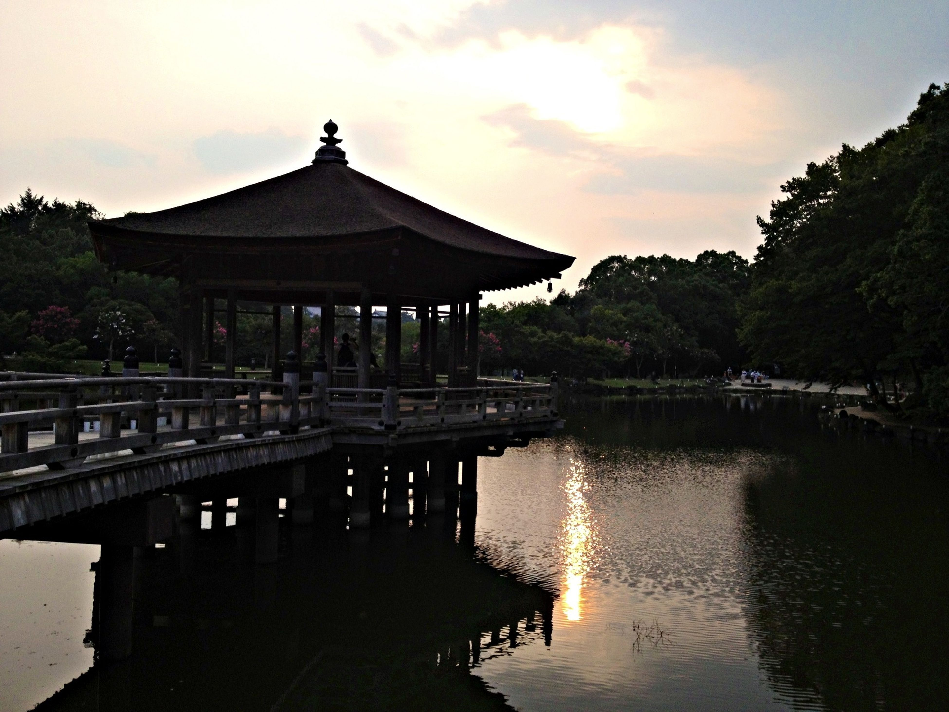 built structure, architecture, water, building exterior, reflection, tree, sky, lake, waterfront, sunset, place of worship, religion, river, spirituality, tranquility, gazebo, temple - building, cloud - sky, nature, tranquil scene
