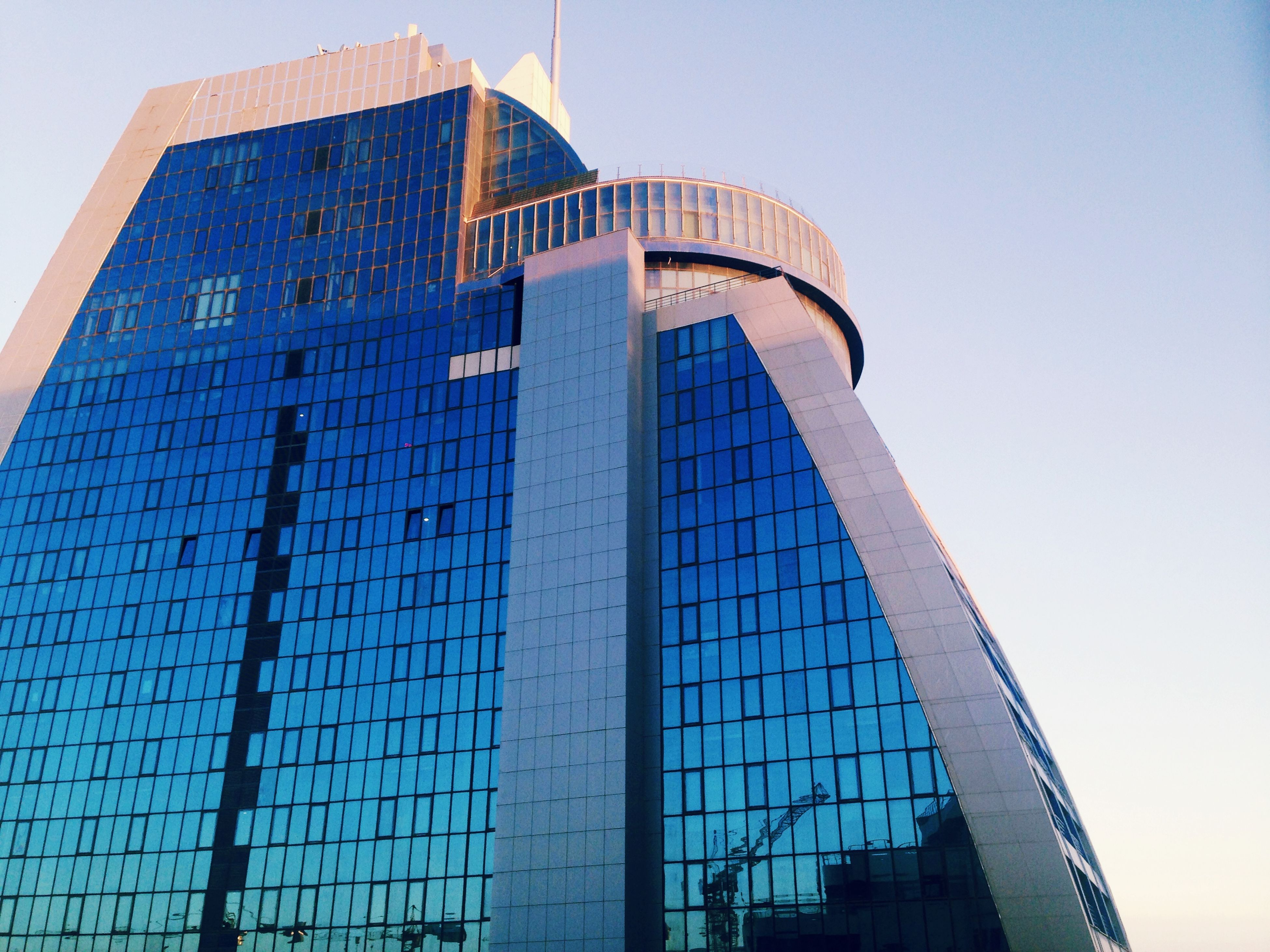 architecture, built structure, building exterior, low angle view, modern, clear sky, city, office building, tower, tall - high, skyscraper, building, sky, glass - material, day, reflection, outdoors, capital cities, no people, travel destinations