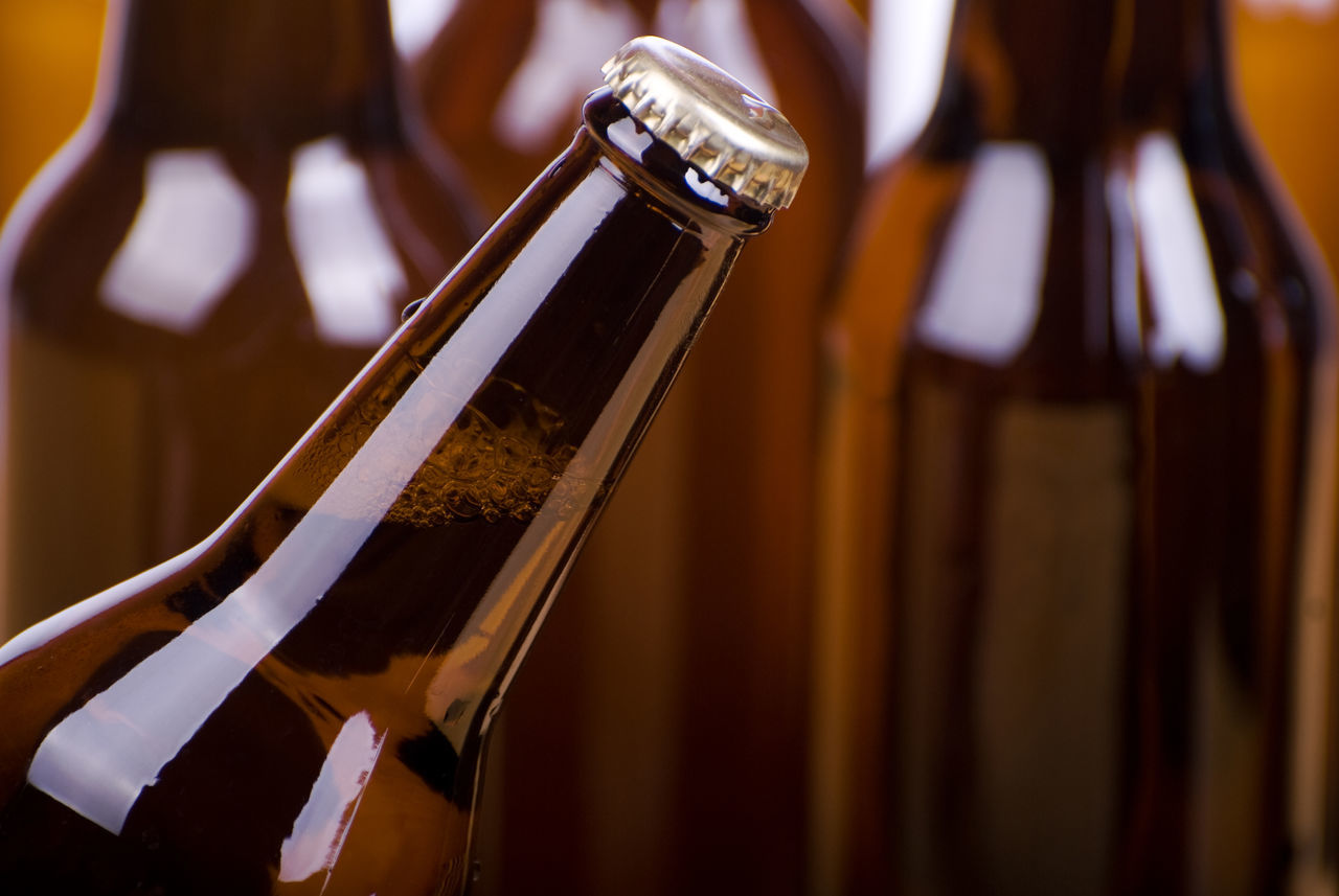 Full brown glass bottle with beer, fresh drink in transparent dark glass. More bottles of alcohol blurred behind. Object in horizontal orientation, nobody in frame. Alcohol Awry Beer Beverage Bottle Bottle Neck Bottles Brown Cap Drink Focus On Foreground Glass Neck No People