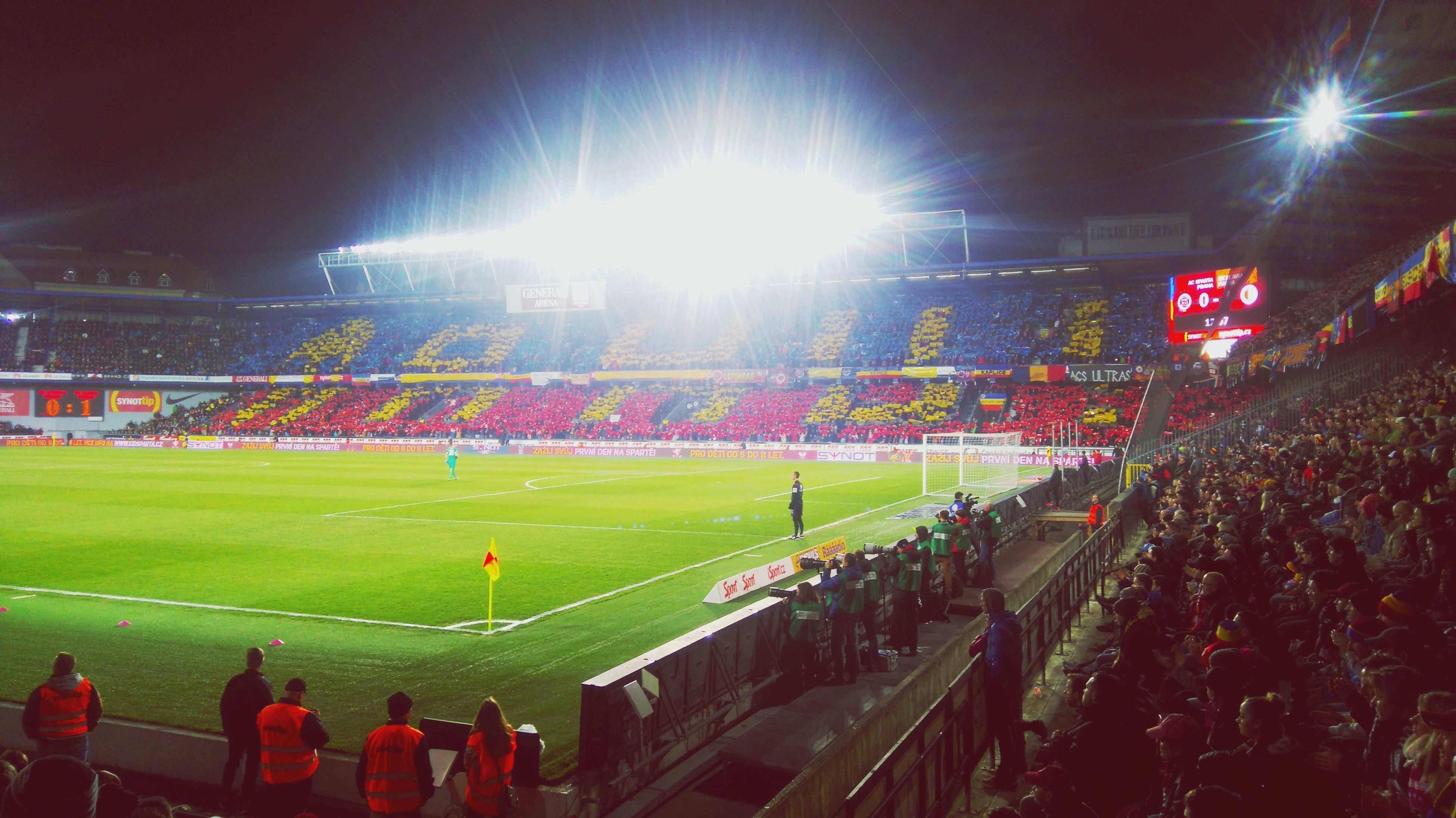 large group of people, stadium, crowd, spectator, sport, real people, soccer, audience, event, men, field, grass, togetherness, leisure activity, playing field, team sport, competition, outdoors, sports team, teamwork, fan - enthusiast, night, illuminated, soccer field, competitive sport, sportsman, sky, people