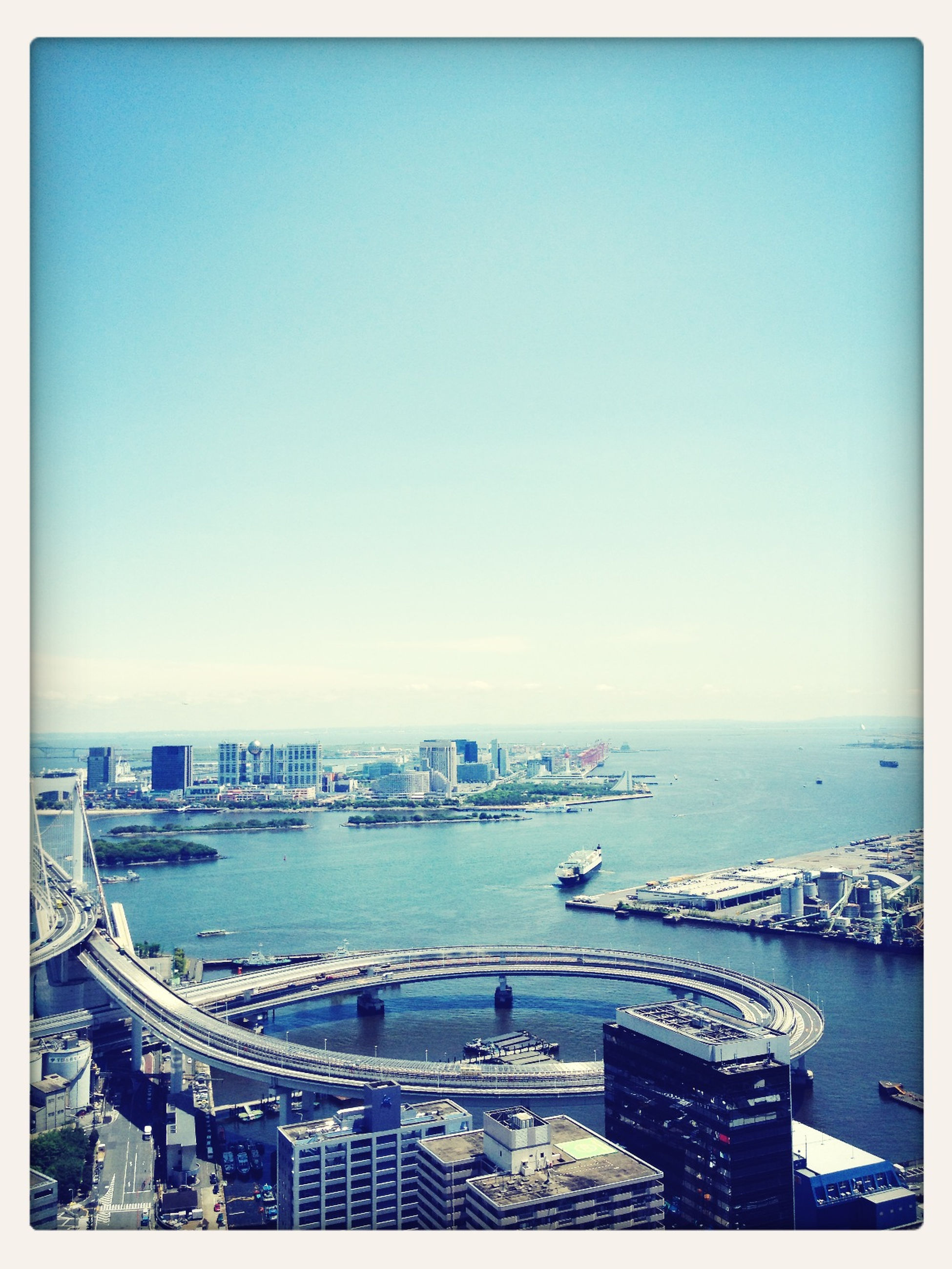 sea, water, transfer print, built structure, architecture, clear sky, blue, horizon over water, auto post production filter, travel destinations, copy space, high angle view, city, building exterior, tourism, travel, transportation, cityscape, nautical vessel, famous place