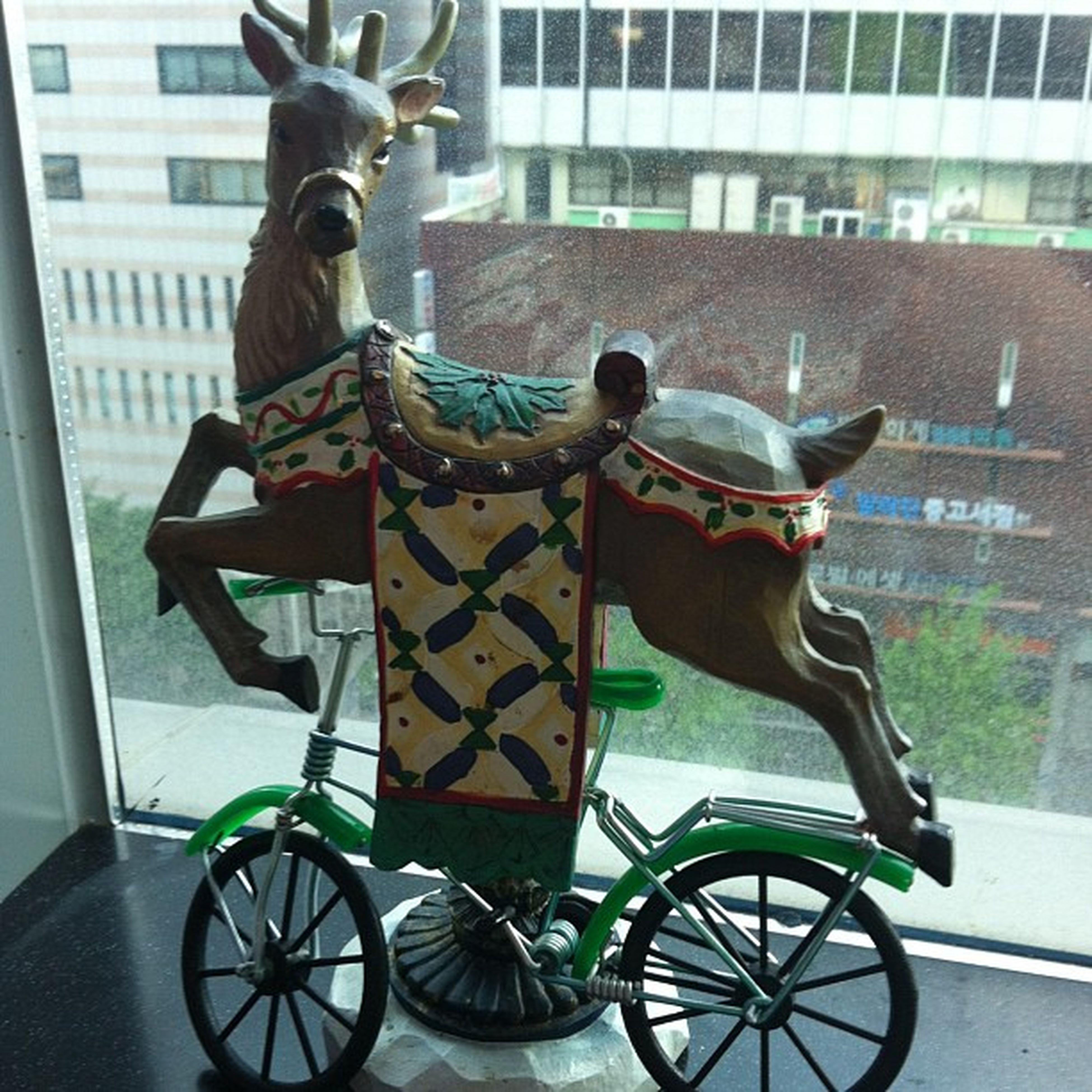 bicycle, building exterior, mode of transport, transportation, animal representation, architecture, land vehicle, built structure, art, art and craft, window, human representation, side view, day, animal themes, sculpture, outdoors, parking, creativity, city