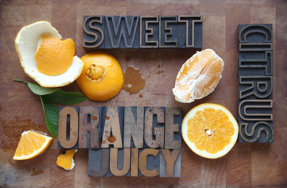A navel orange with peeled, halved, and cut sections and descriptive words with spilled juice on a cutting boardorange Citrus Fruit Cut Cutting Board Food Food Preparation Fresh Fruit Freshness Fruit Peel Halves Healthy Eating Juicy Leaves Letters Navel Nobody Orange Overhead View Sections SLICE Sweet Type Typography Words