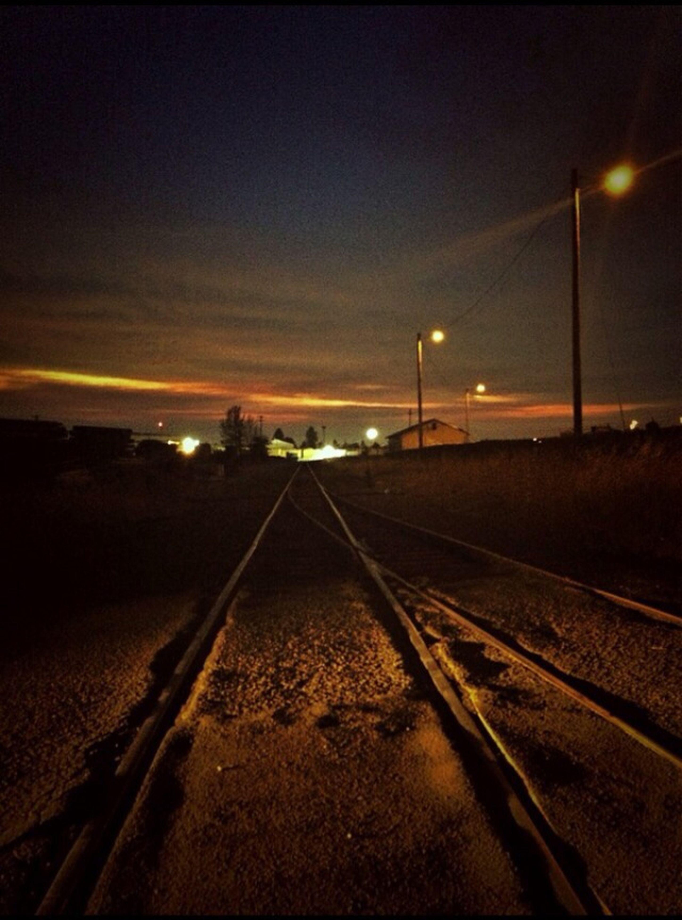 transportation, the way forward, railroad track, diminishing perspective, vanishing point, illuminated, sky, rail transportation, road, night, sunset, road marking, street light, dusk, long, surface level, straight, empty, outdoors, no people