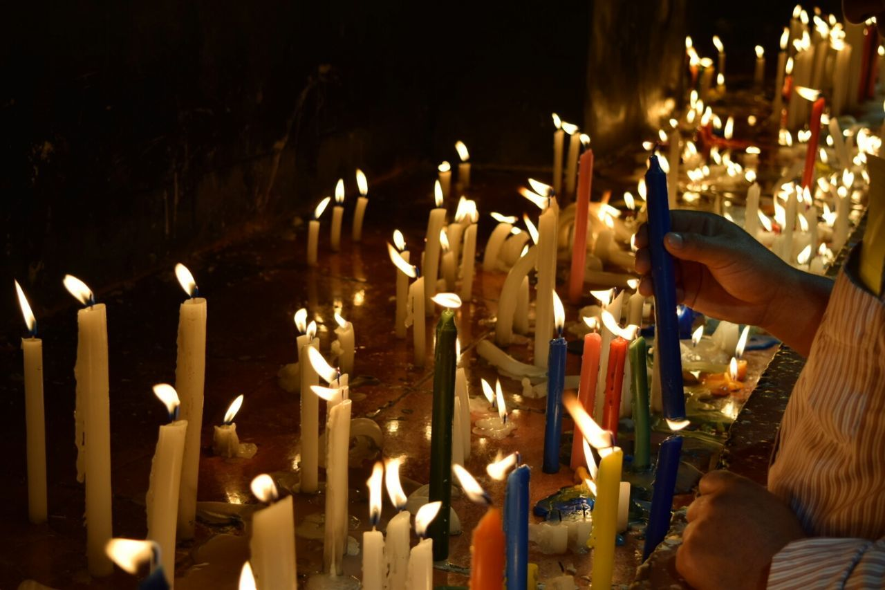 Close-Up Of Hand Holding Illuminated Candles In Temple