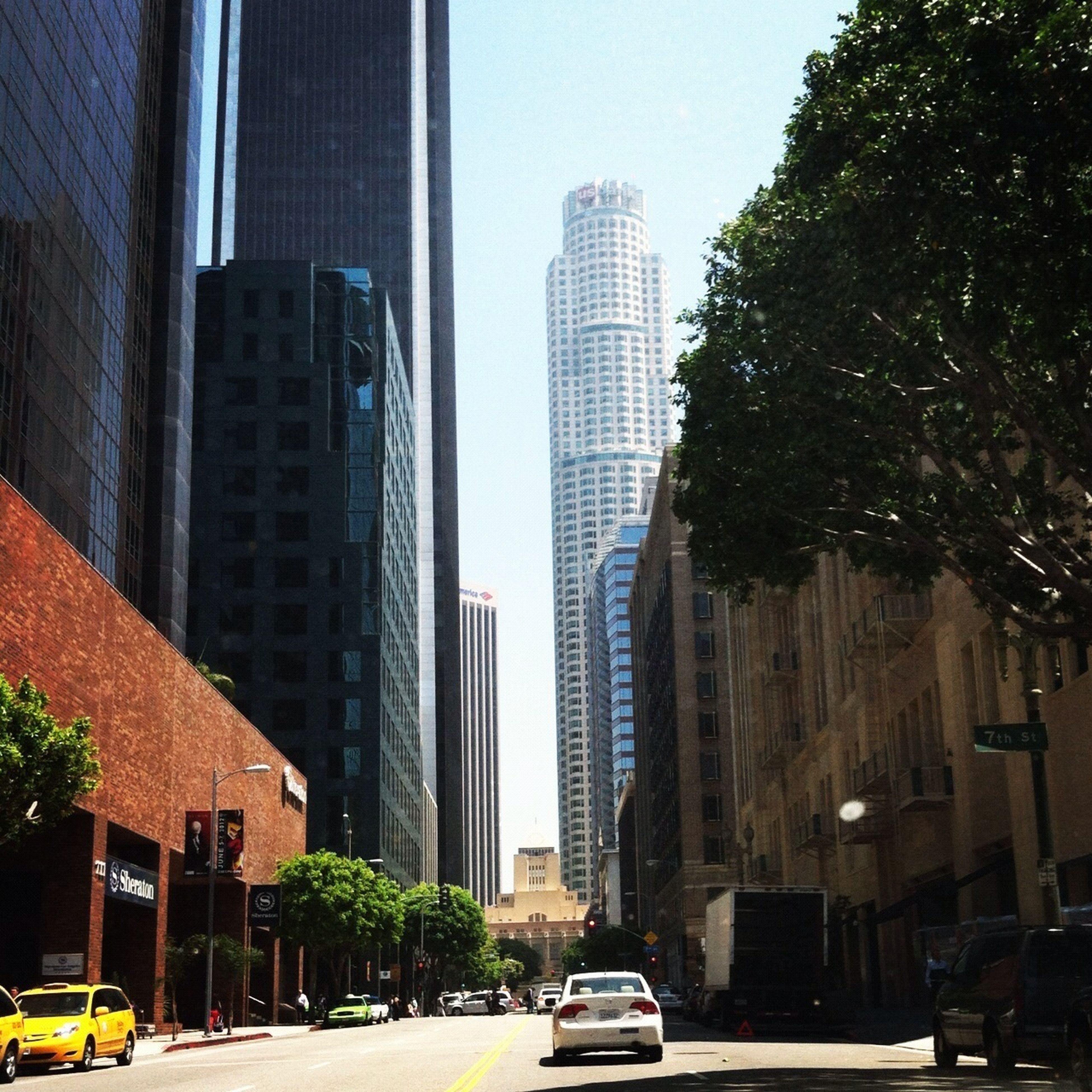 building exterior, architecture, built structure, city, car, transportation, land vehicle, skyscraper, mode of transport, street, office building, road, modern, tall - high, tower, city life, building, traffic, tree, city street