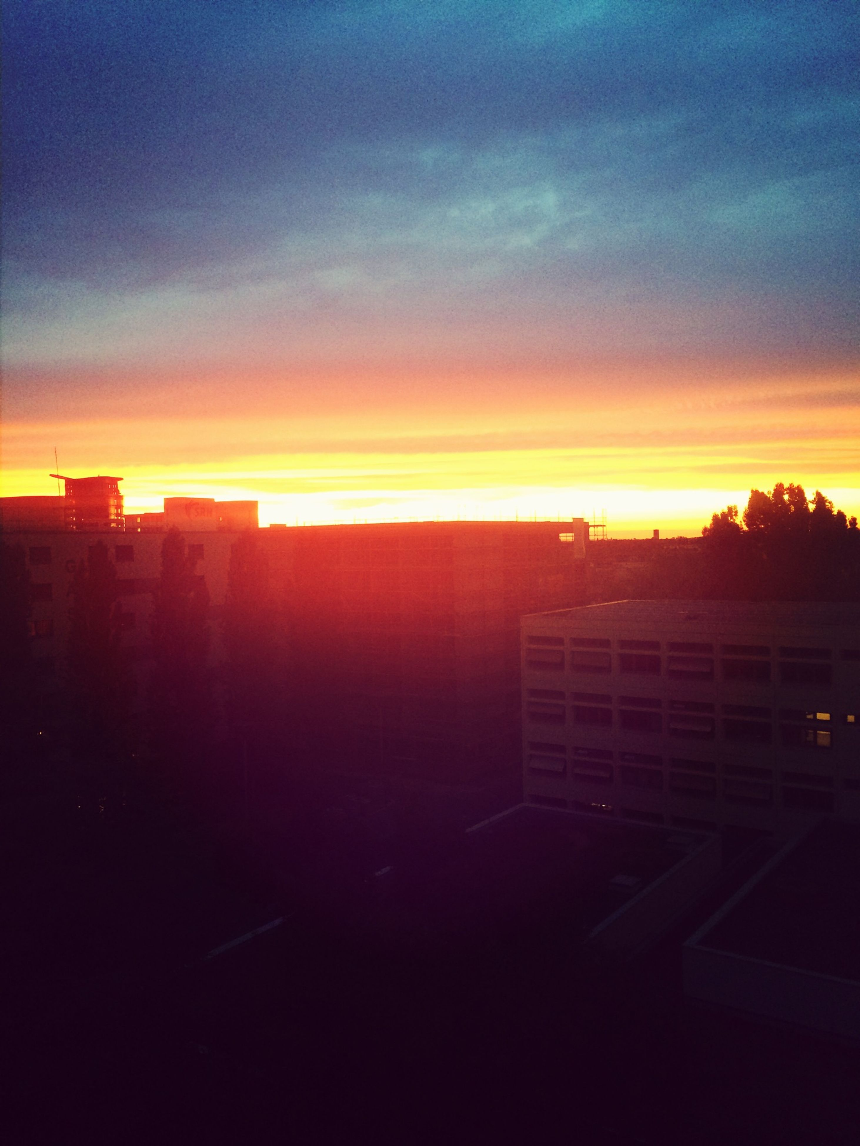 sunset, sun, building exterior, orange color, architecture, sky, built structure, cloud - sky, silhouette, city, sunlight, sunbeam, scenics, beauty in nature, nature, no people, cloud, lens flare, outdoors, residential building