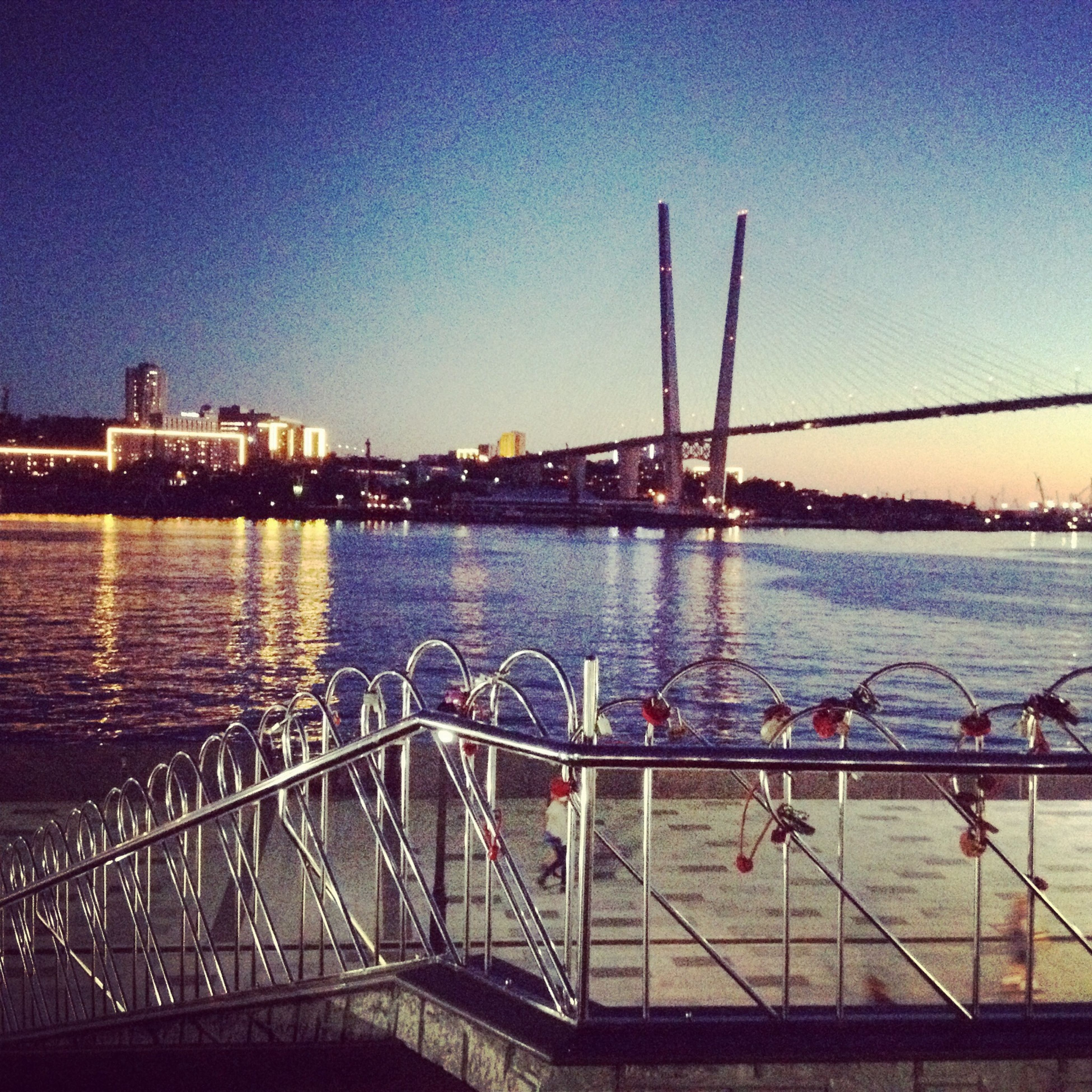 water, built structure, architecture, transportation, bridge - man made structure, river, clear sky, connection, illuminated, city, suspension bridge, nautical vessel, engineering, bridge, building exterior, blue, waterfront, sky, sea, travel destinations
