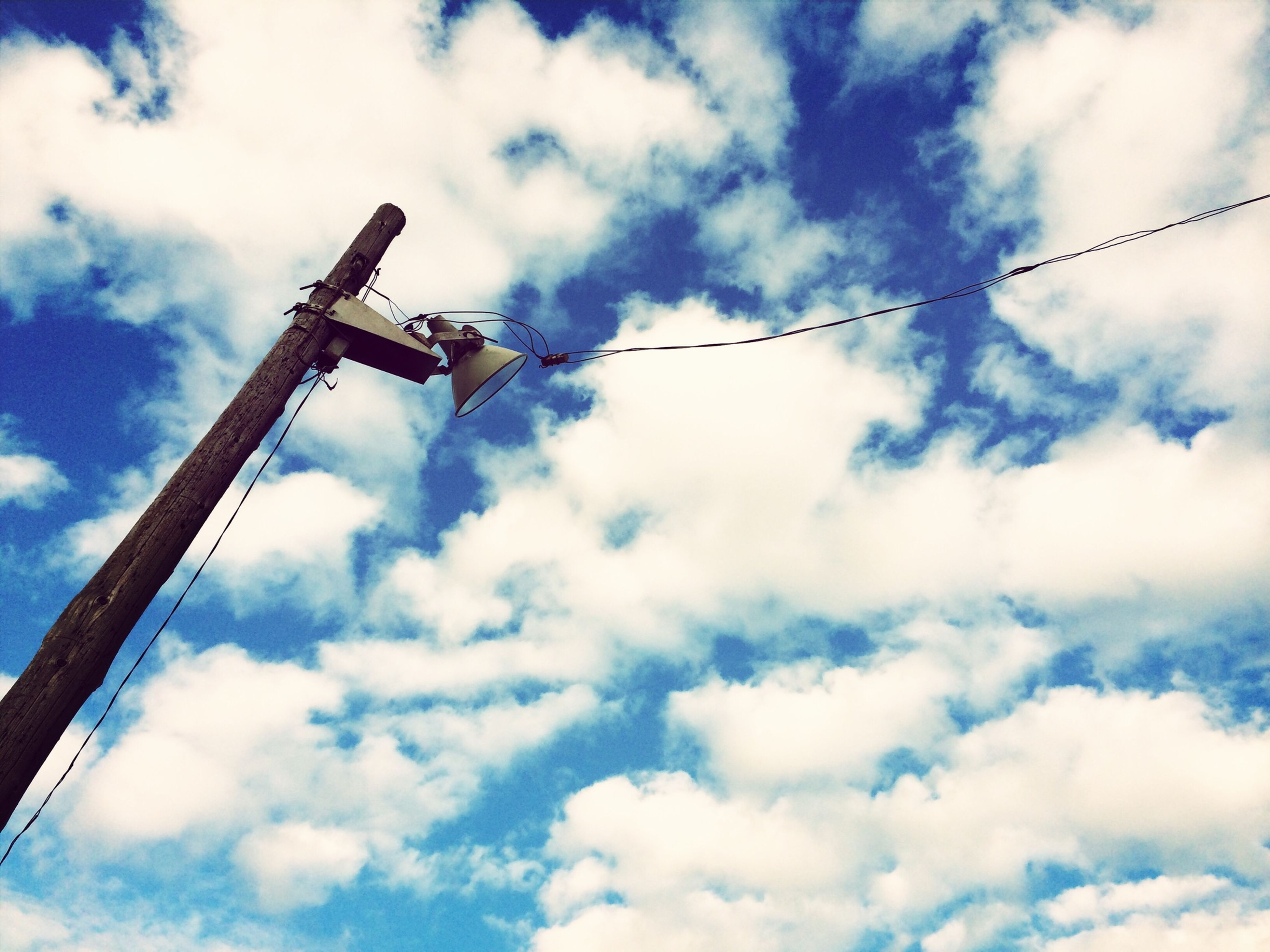 low angle view, sky, cloud - sky, cloudy, fuel and power generation, cloud, technology, electricity, connection, day, outdoors, no people, metal, crane - construction machinery, environmental conservation, lighting equipment, industry, pole, cable, power supply