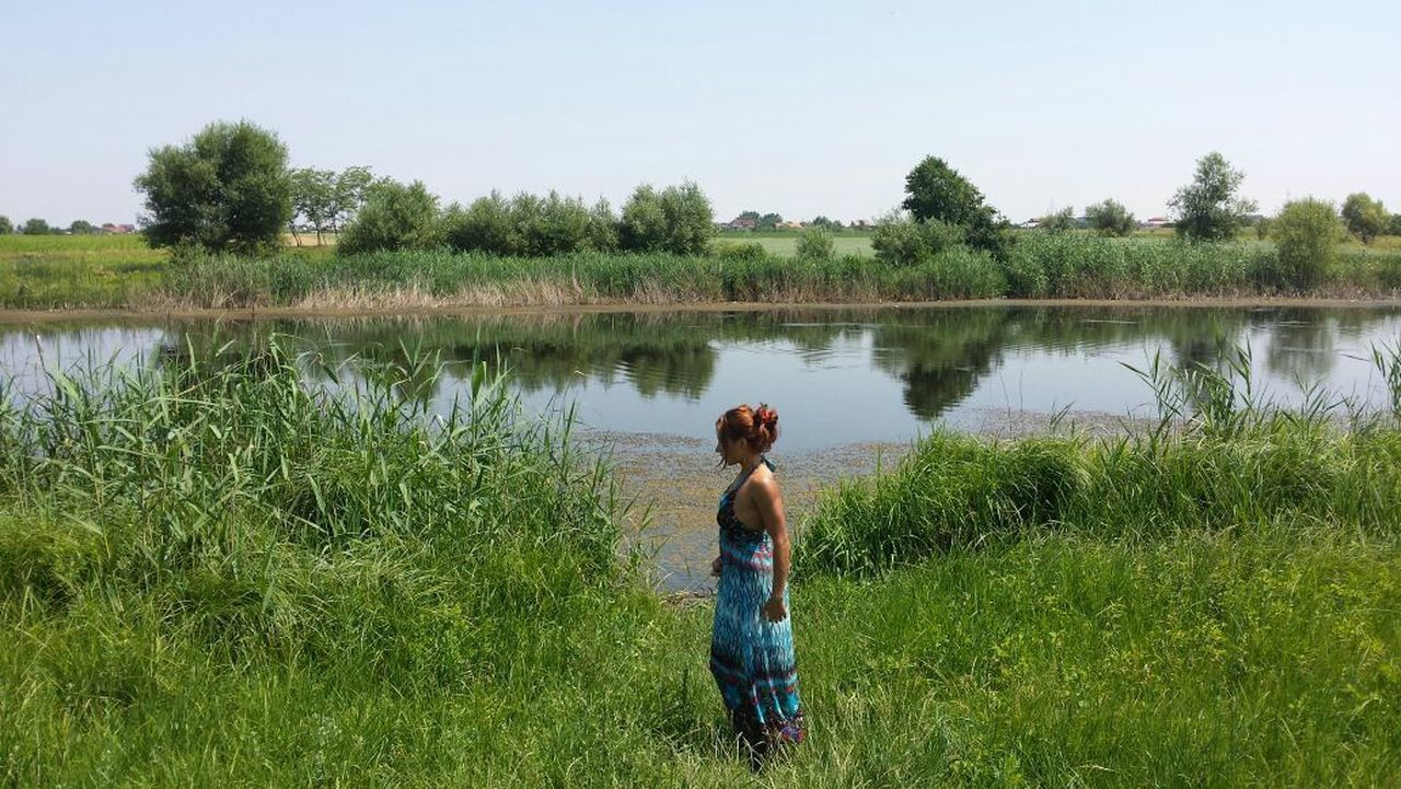 grass, rear view, nature, real people, water, lake, growth, beauty in nature, tree, leisure activity, day, outdoors, tranquil scene, standing, field, scenics, plant, tranquility, green color, men, women, lifestyles, sky, full length, mammal, people