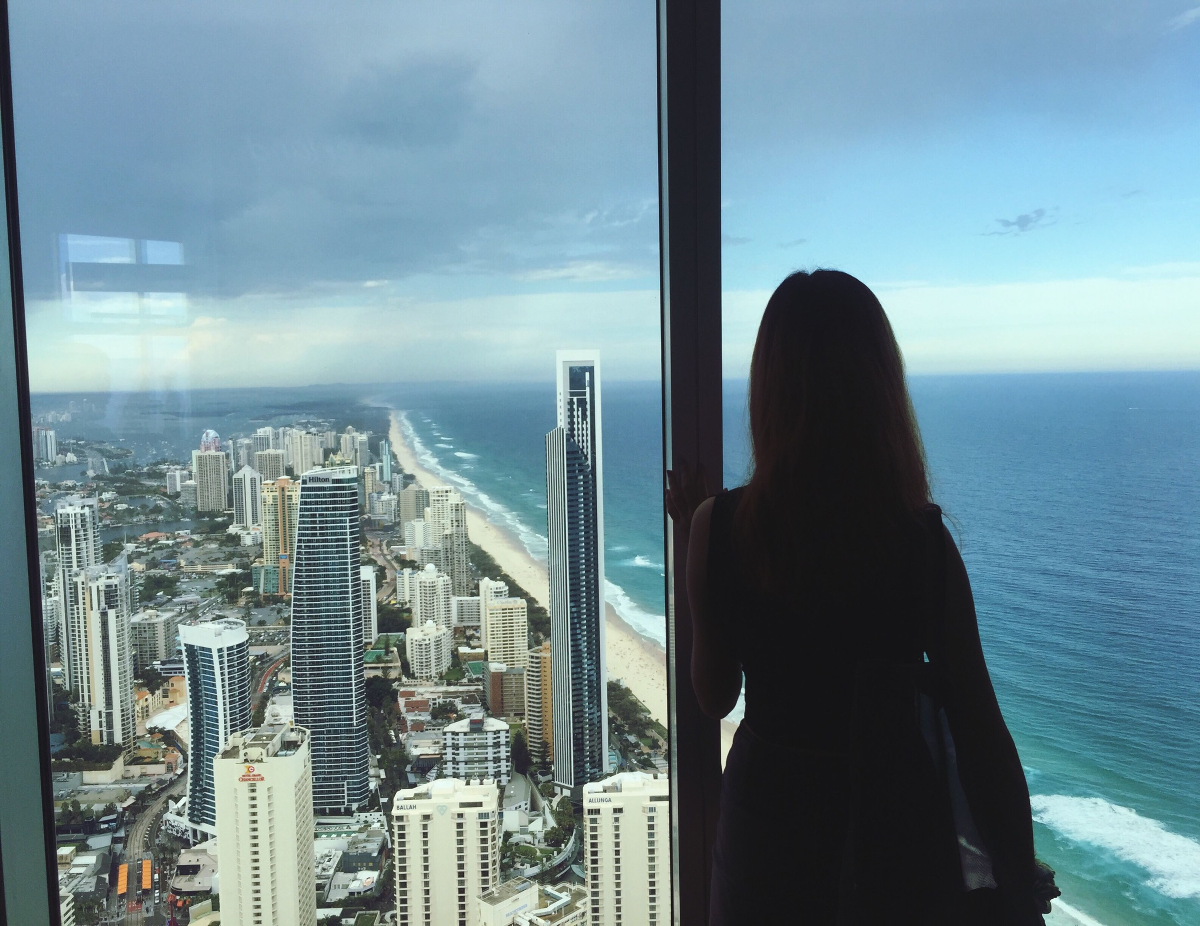 sea, horizon over water, sky, rear view, water, indoors, lifestyles, cityscape, looking at view, person, leisure activity, city, architecture, built structure, window, standing, cloud - sky, men