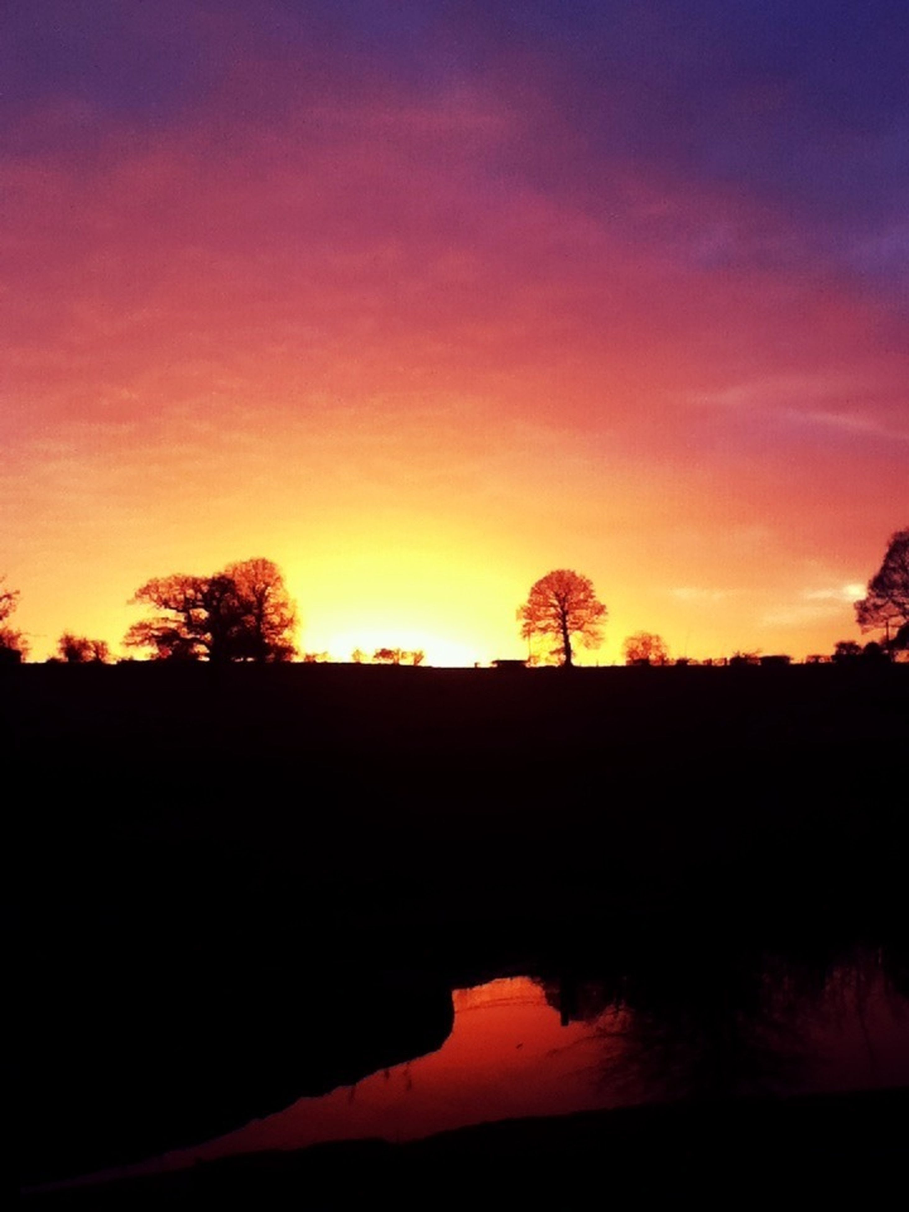 sunset, silhouette, scenics, orange color, tranquil scene, beauty in nature, tranquility, sky, tree, idyllic, nature, dramatic sky, cloud - sky, landscape, dark, water, outdoors, moody sky, cloud, majestic