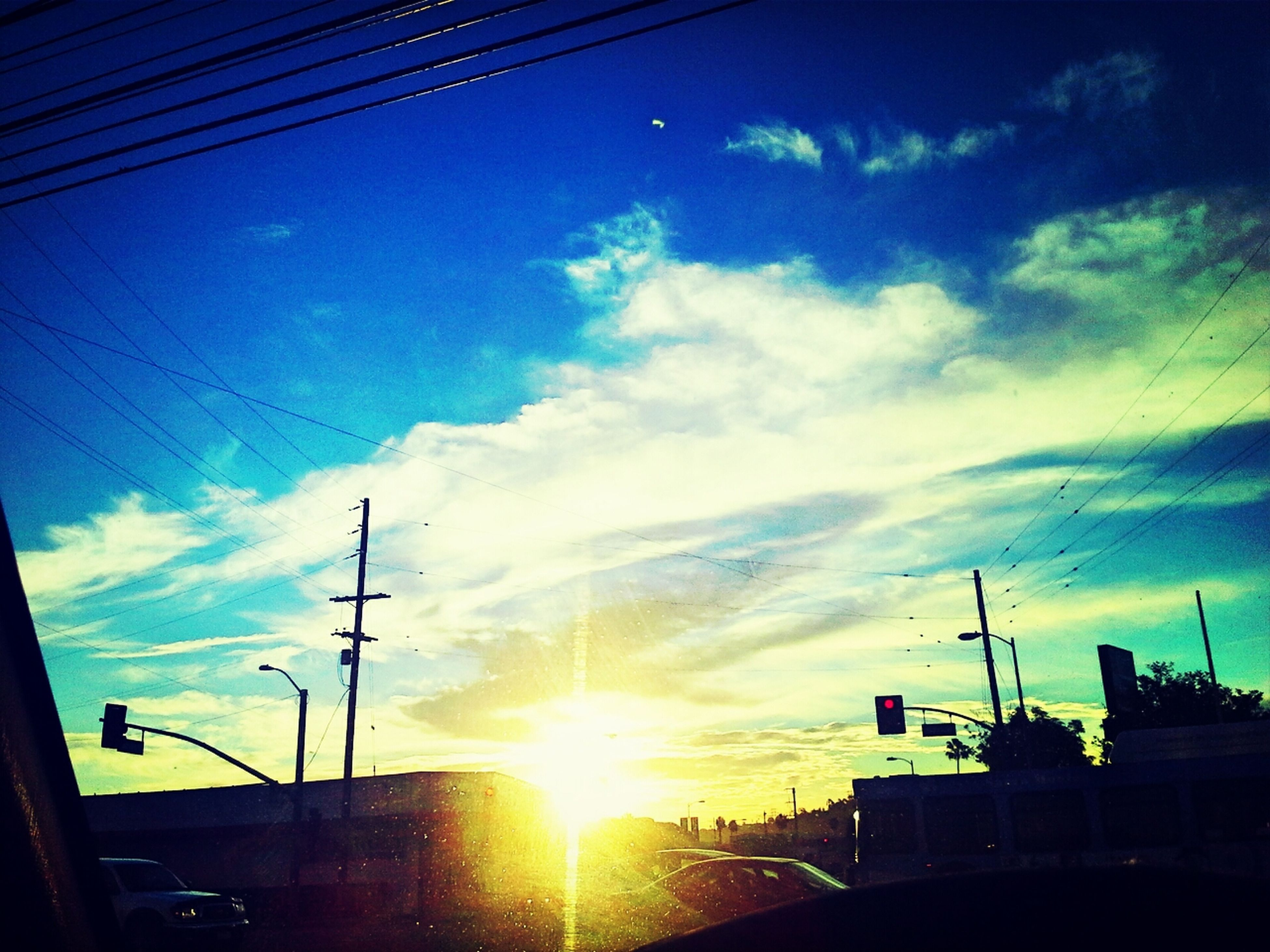 building exterior, built structure, sky, sunset, sun, architecture, silhouette, low angle view, power line, sunlight, sunbeam, electricity pylon, cloud - sky, cable, cloud, electricity, lens flare, house, car, power supply