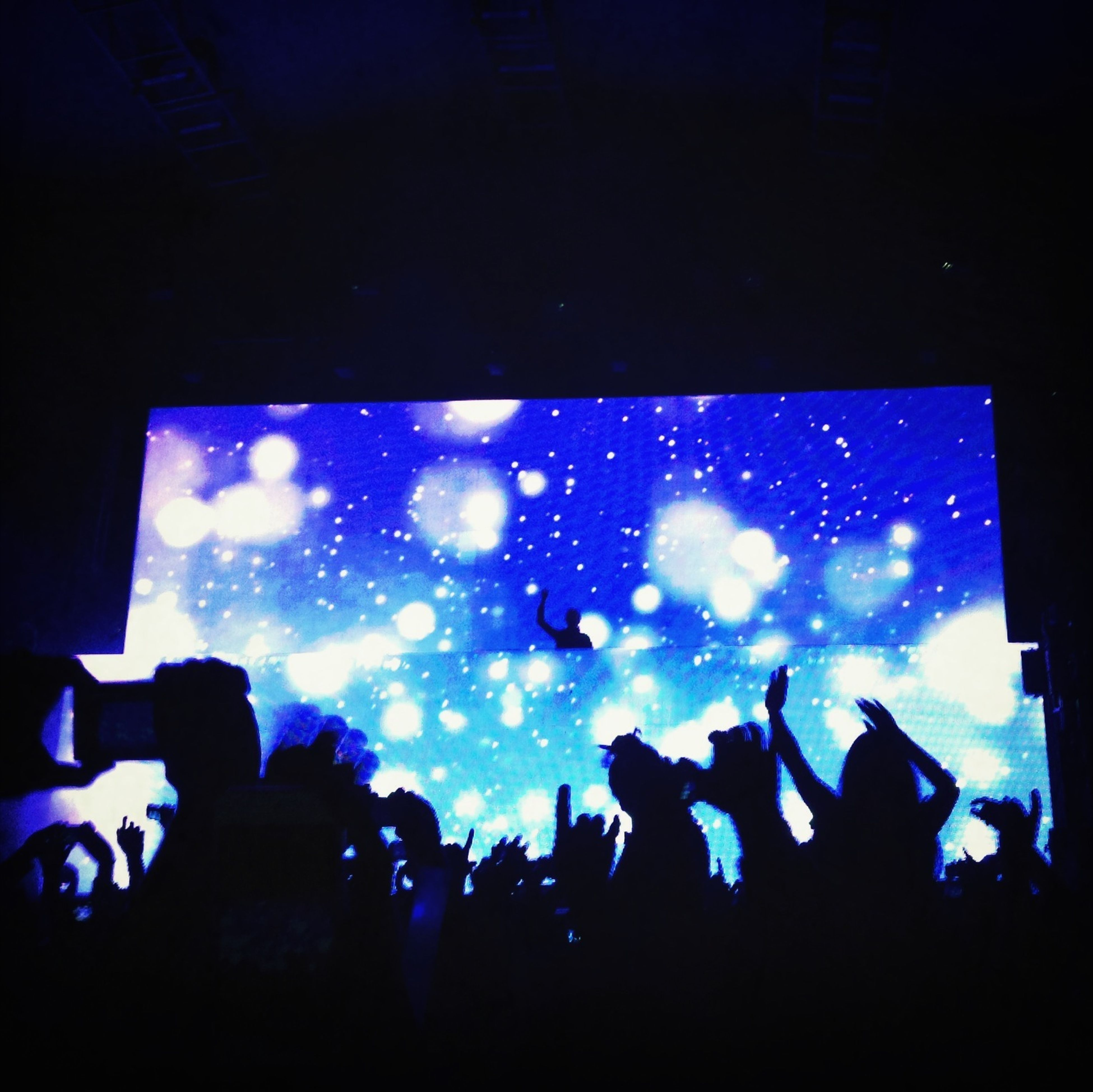 blue, silhouette, indoors, large group of people, night, illuminated, sky, men, crowd, leisure activity, nightlife, unrecognizable person, lifestyles, concert, person, glass - material, light - natural phenomenon, arts culture and entertainment, window