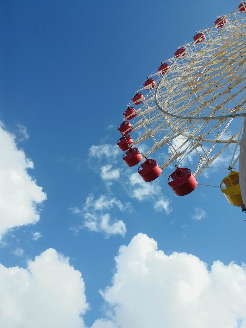 amusement park, low angle view, arts culture and entertainment, sky, cloud - sky, amusement park ride, red, blue, day, no people, outdoors, leisure activity, ferris wheel