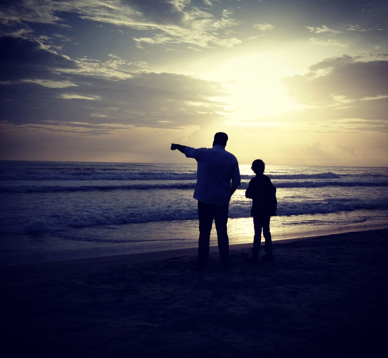 sea, beach, sunset, horizon over water, silhouette, sky, nature, water, togetherness, two people, scenics, sand, standing, beauty in nature, tranquil scene, real people, vacations, leisure activity, love, men, outdoors, full length, bonding, childhood, friendship, day, people