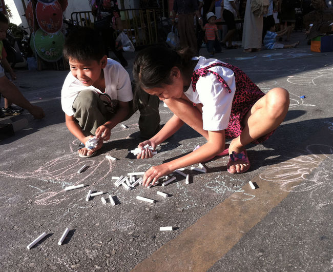 Boys Casual Clothing Chalk Childhood Children Elementary Age Enjoyment Full Length Fun Girls Leisure Activity Lifestyles On The Floor Outdoors Person Playing Playing On The Streets Sitting Spotted In Thailand Street Sun Sunlight Sunlight Thailand Togetherness
