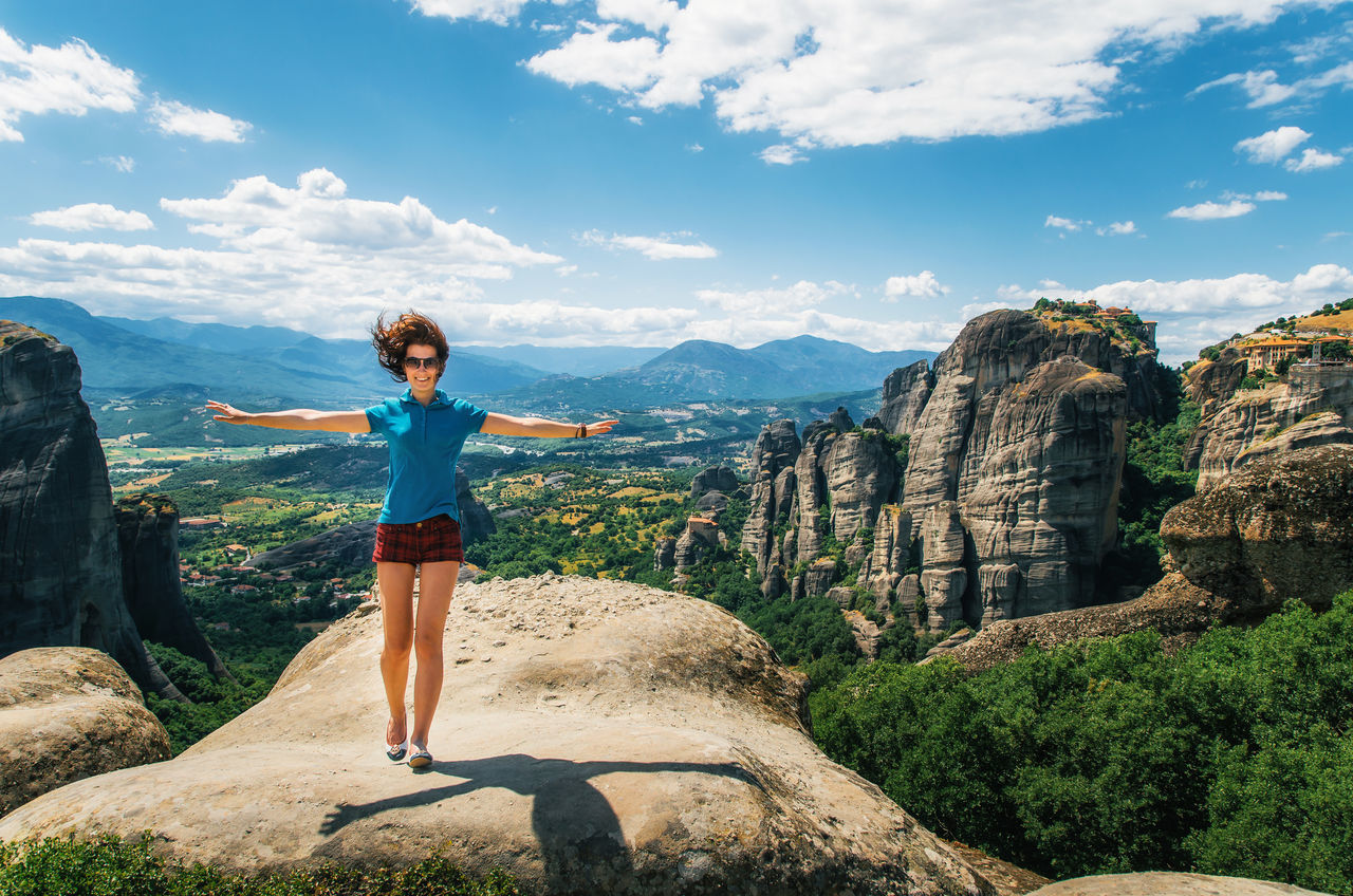 Portrait Of Happy Woman With Arms Outstretched Standing On Rock Against Landscape