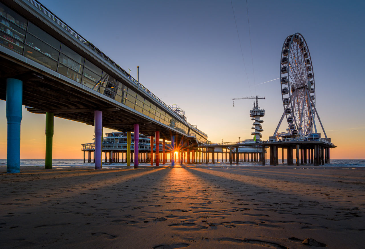 The famous landmark The Pier in Scheveningen as seen from the beach . Architecture Beach Built Structure Day Landmark Netherlands No People Outdoors Pier Sand Scheveningen  Scheveningen Pier Shore Sky Sunset The Hague Travel Water