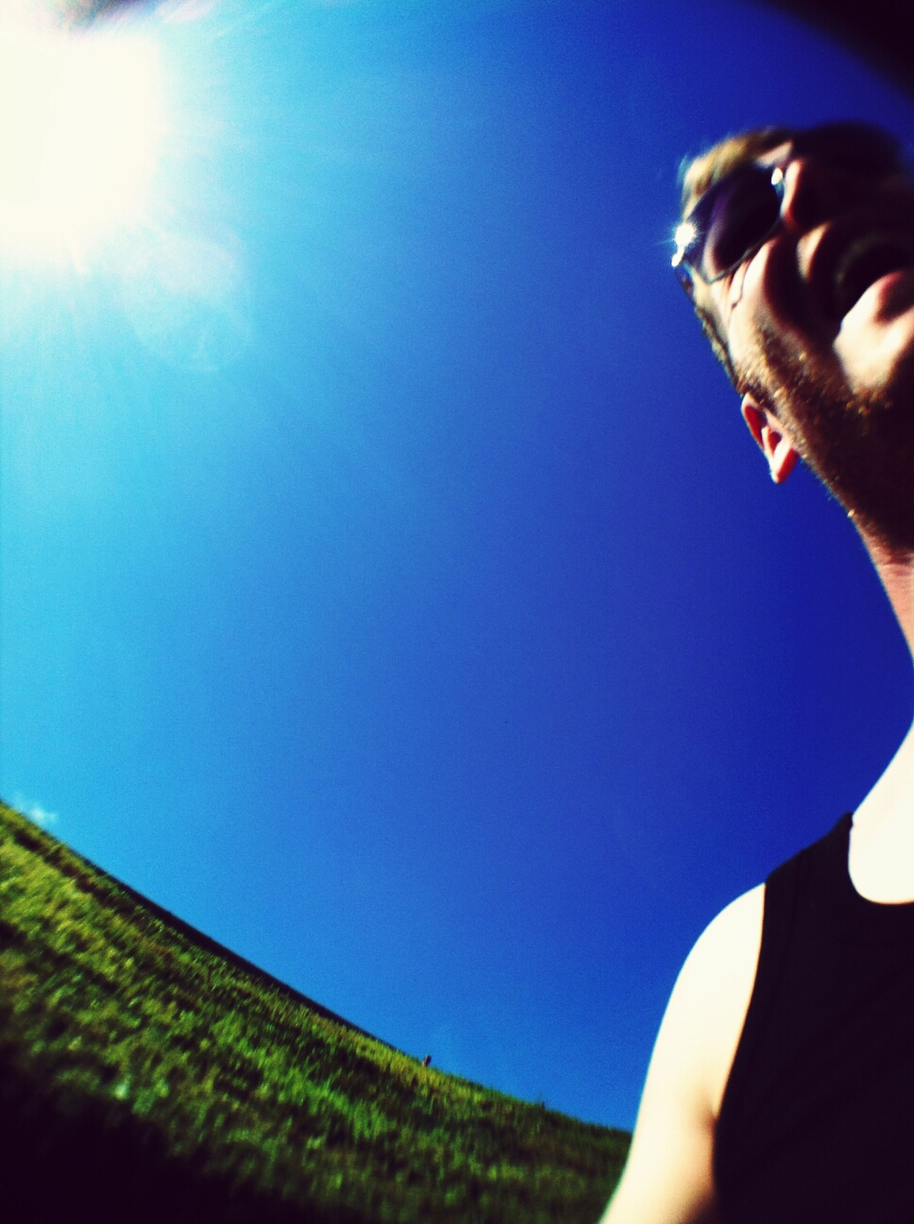 blue, person, part of, clear sky, cropped, lifestyles, personal perspective, leisure activity, unrecognizable person, sky, low angle view, copy space, sunlight, human finger, men, low section