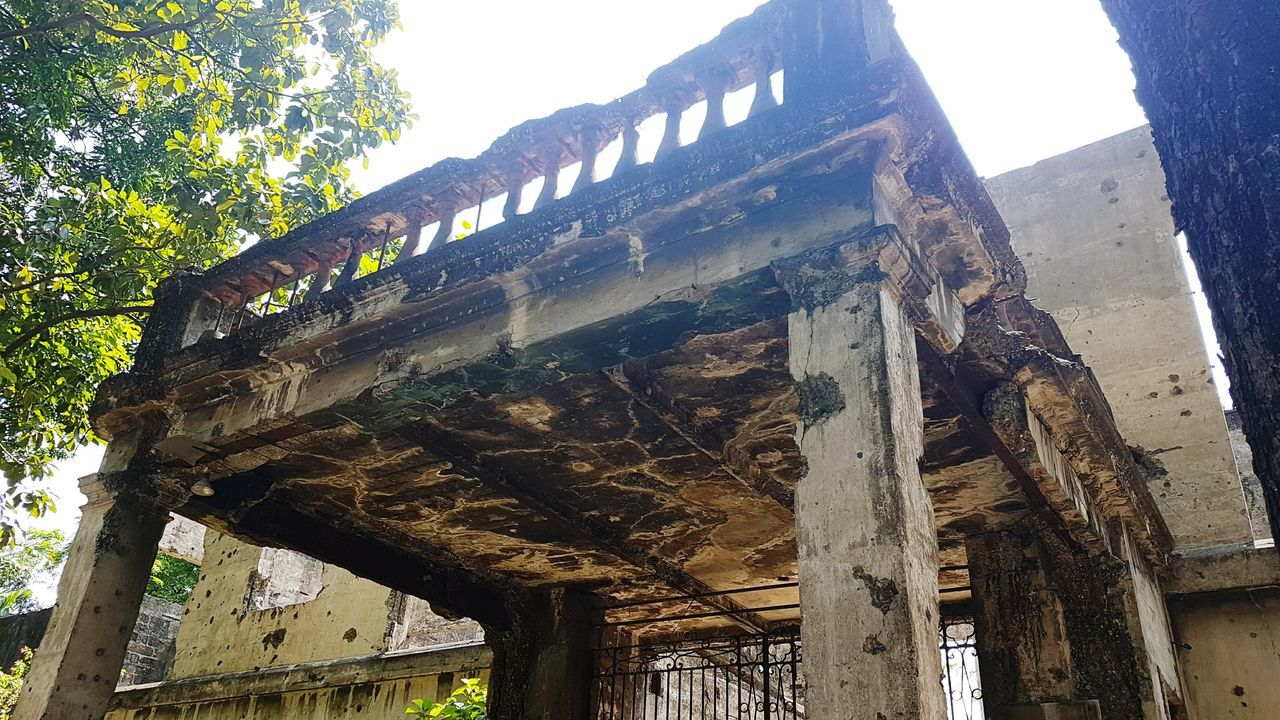 low angle view, built structure, architecture, old, history, old ruin, architectural column, day, no people, weathered, ancient, wood - material, outdoors, damaged, abandoned, building exterior, ancient civilization, sky, tree, nature