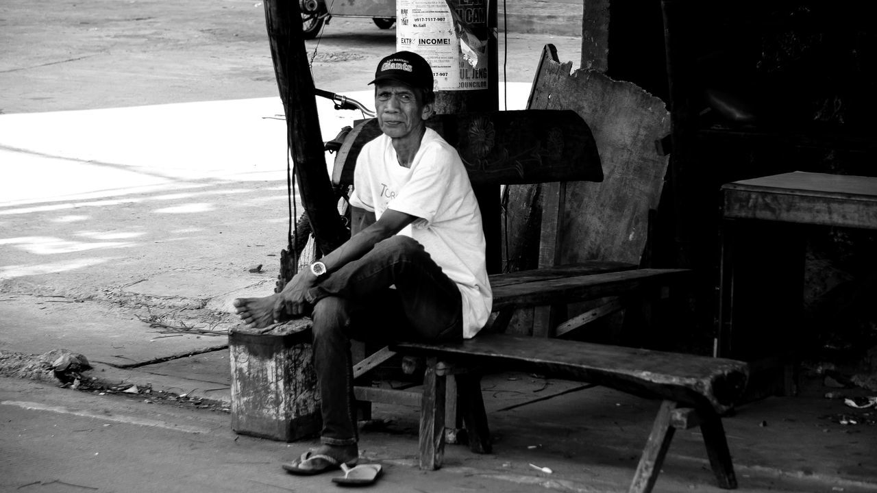 A man sitting on a bench beside the road. Bench Black And White Casual Clothing EyeEm Pampanga Eyeem Philippines Lifestyles Man Natural Light Portrait Outdoors Sitting Street Photography Street Portrait Wood - Material Wooden Bench Sony A6000 Monochrome Photography