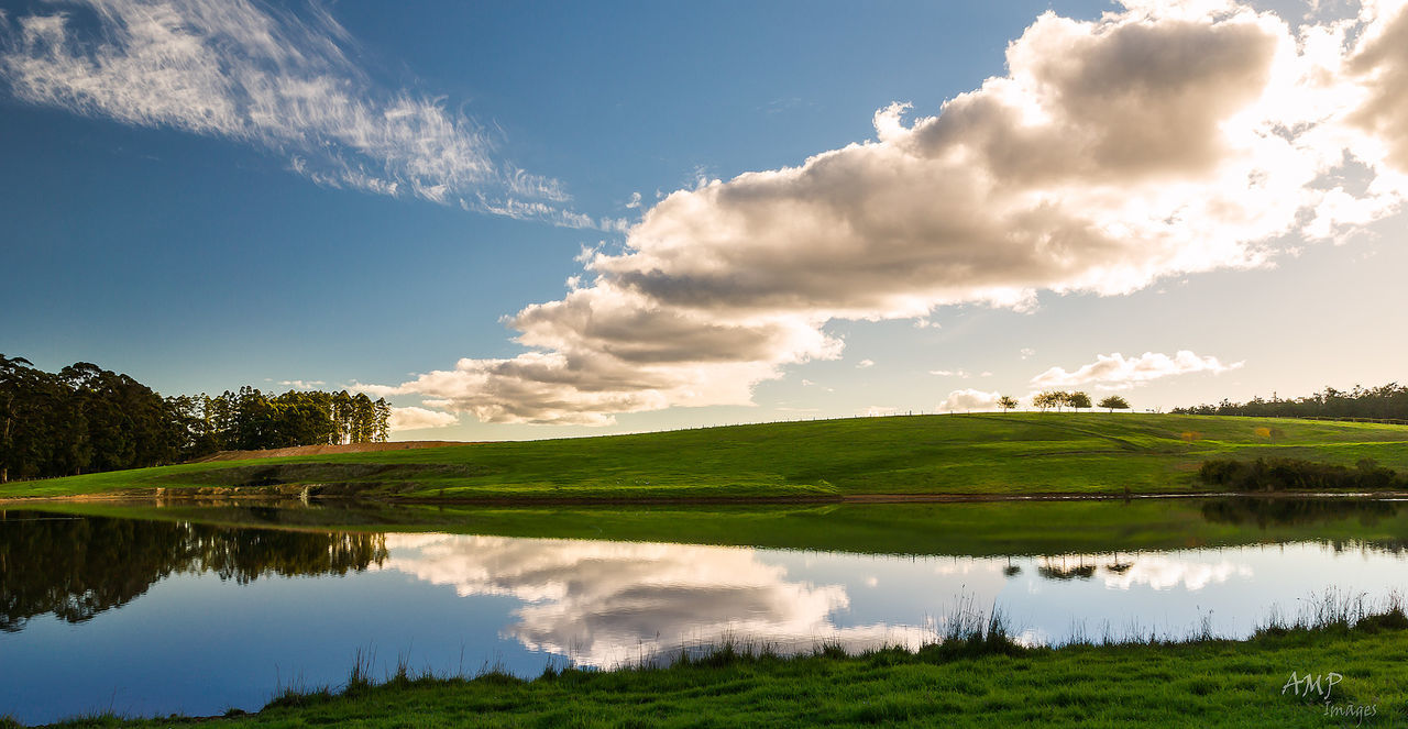 water, reflection, sky, tranquility, tranquil scene, scenics, grass, beauty in nature, lake, cloud - sky, nature, cloud, majestic, day, standing water, non-urban scene, blue, green color, calm, remote, no people, grassy, bright, cumulus cloud, cloudy, green, solitude