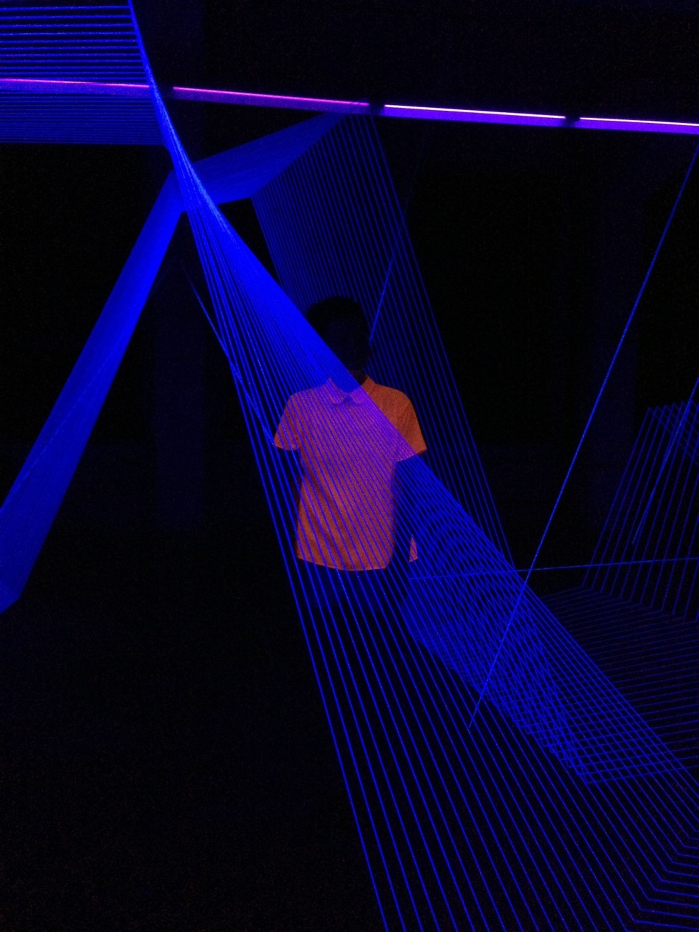 illuminated, night, blue, low angle view, lighting equipment, arts culture and entertainment, pattern, metal, light - natural phenomenon, multi colored, indoors, built structure, no people, railing, connection, copy space, electricity, modern, electric light