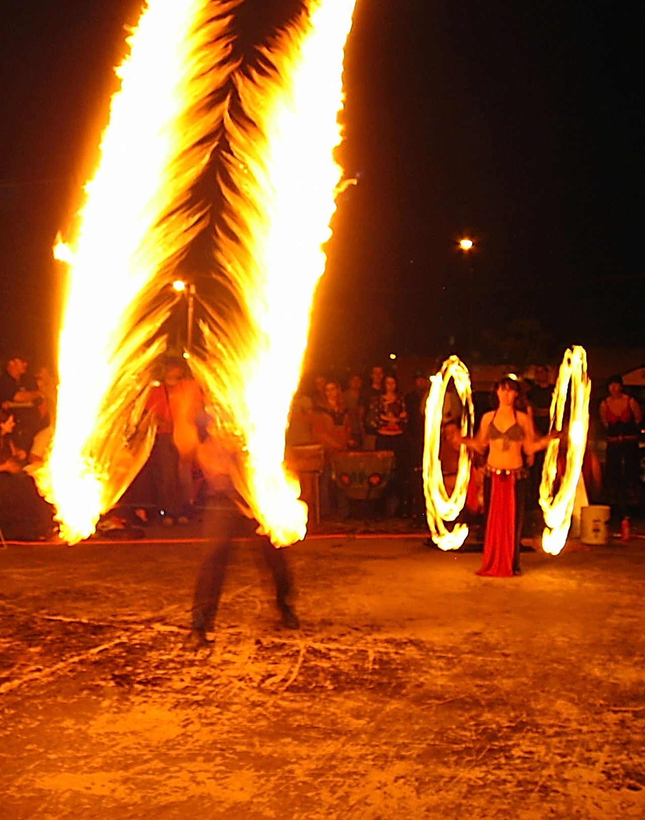 Arts Culture And Entertainment Burning Celebration Dancer Dancing Expertise Flame Full Length Fun Heat - Temperature Illuminated Large Group Of People Leisure Activity Lifestyles Long Exposure Men Motion Night Performance Performing Arts Event Real People Skill  Strength Togetherness Women