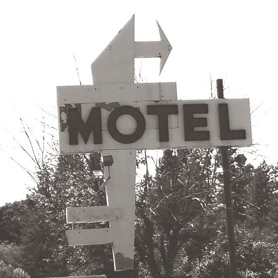 Arrow Symbol No People Sign Motel Sign Black And White Text Guidance Communication Sky Road Sign Outdoors Day Clear Sky Tree