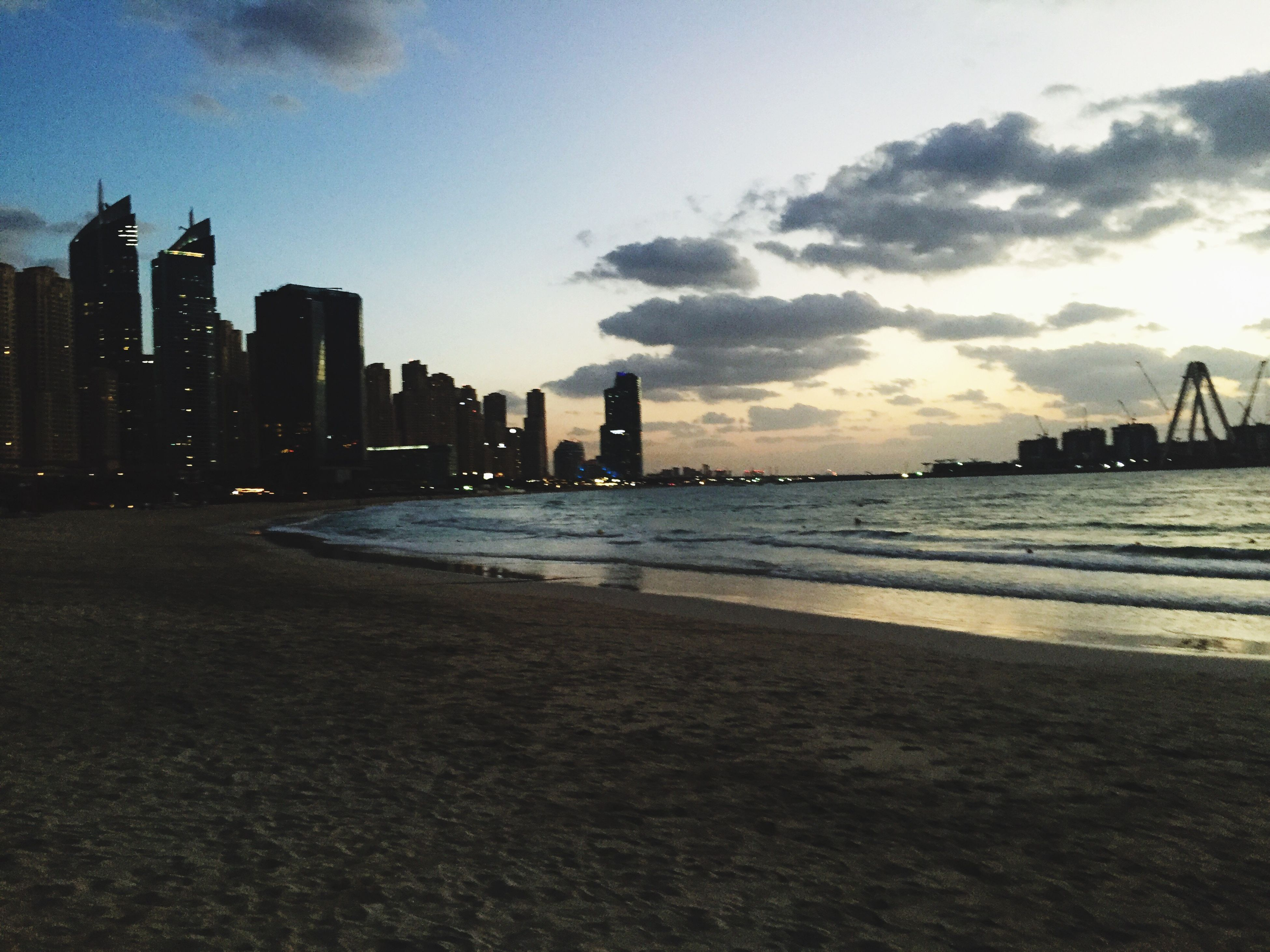city, architecture, skyscraper, building exterior, built structure, sea, modern, sky, sunset, urban skyline, water, cityscape, outdoors, beach, cloud - sky, travel destinations, sand, no people, downtown district, day