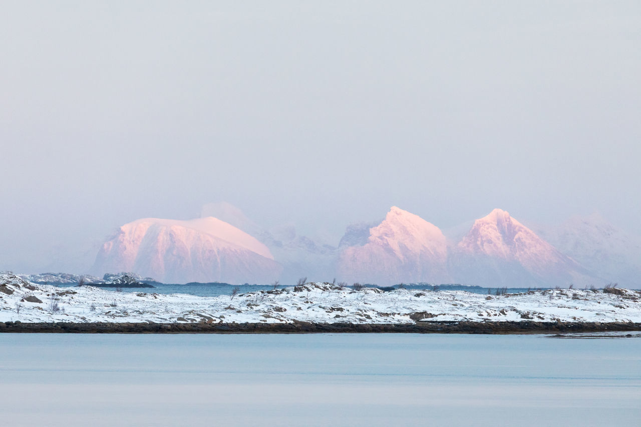 Snowcapped mountain range illuminated by sunlight during sunset Beauty In Nature Clear Sky Cold Temperature Copy Space Distant Dramatic Landscape Extreme Terrain Illuminated Island Landscape Lofoten And Vesteral Islands Mountain Mountain Range Pastel Colored Remote Rock - Object Scenics Sea Sky Snow Snowcapped Mountain Sunlight Sunset Waterfront Winter The Great Outdoors - 2017 EyeEm Awards