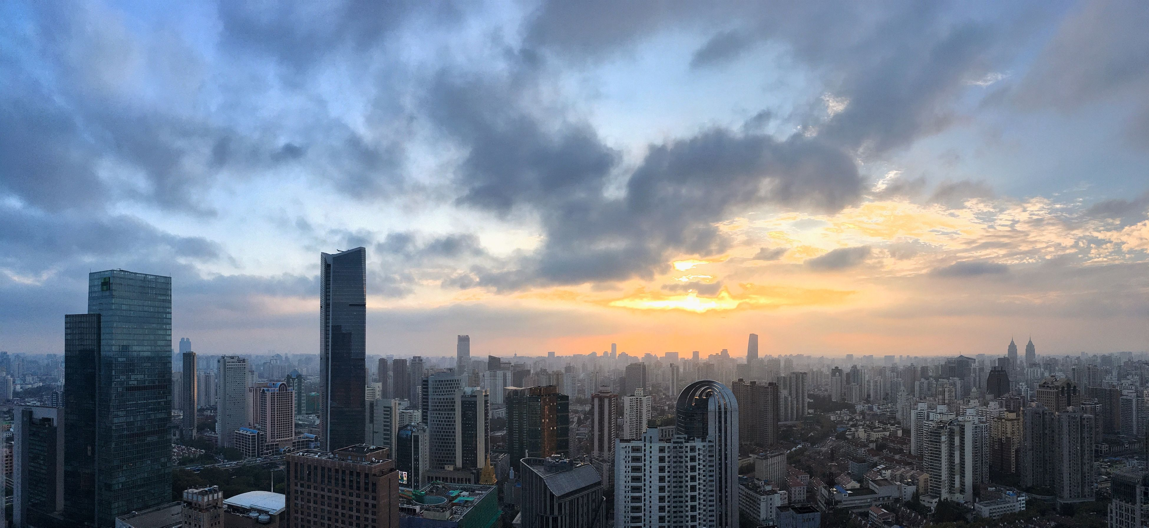 city, cityscape, building exterior, skyscraper, architecture, built structure, sky, sunset, cloud - sky, tall - high, modern, tower, crowded, office building, urban skyline, city life, financial district, cloud, high angle view, cloudy
