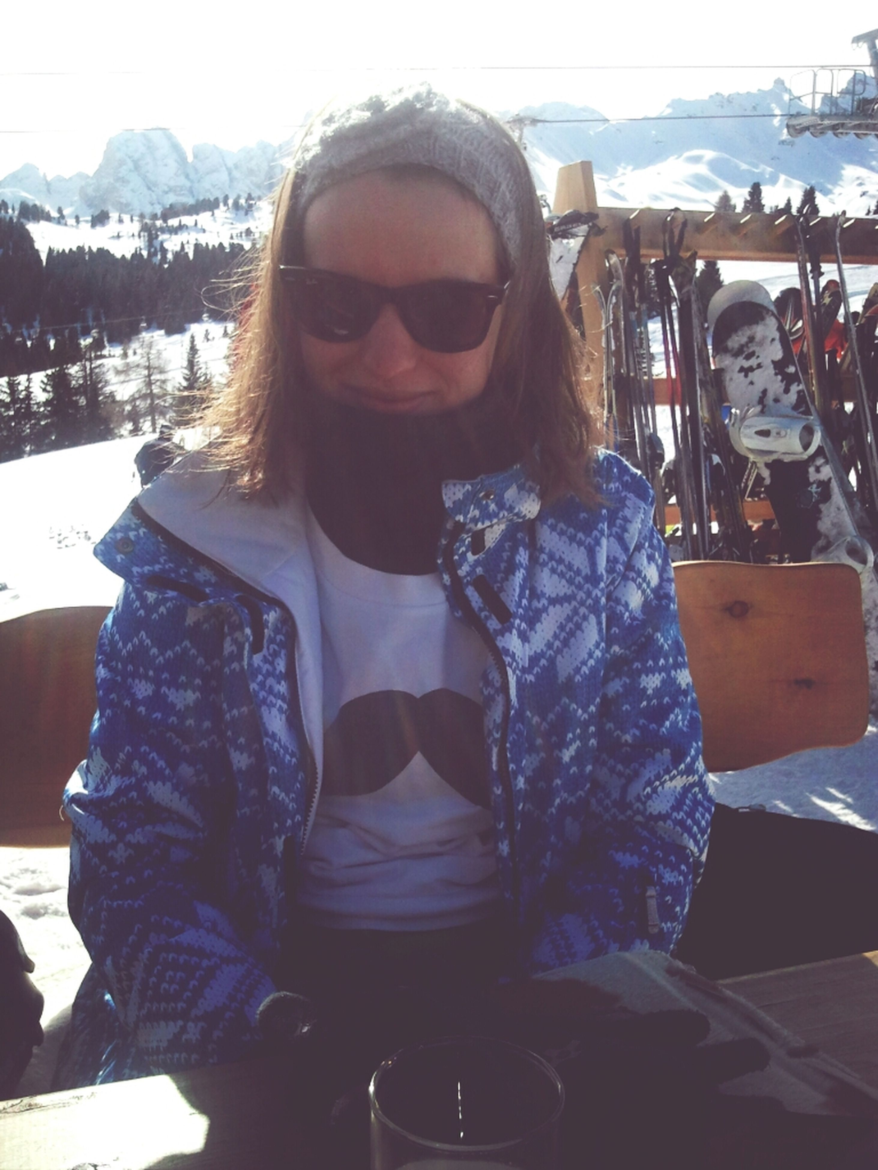 winter, cold temperature, lifestyles, snow, leisure activity, person, sunglasses, casual clothing, portrait, young adult, looking at camera, warm clothing, front view, mountain, sitting, smiling, season, waist up