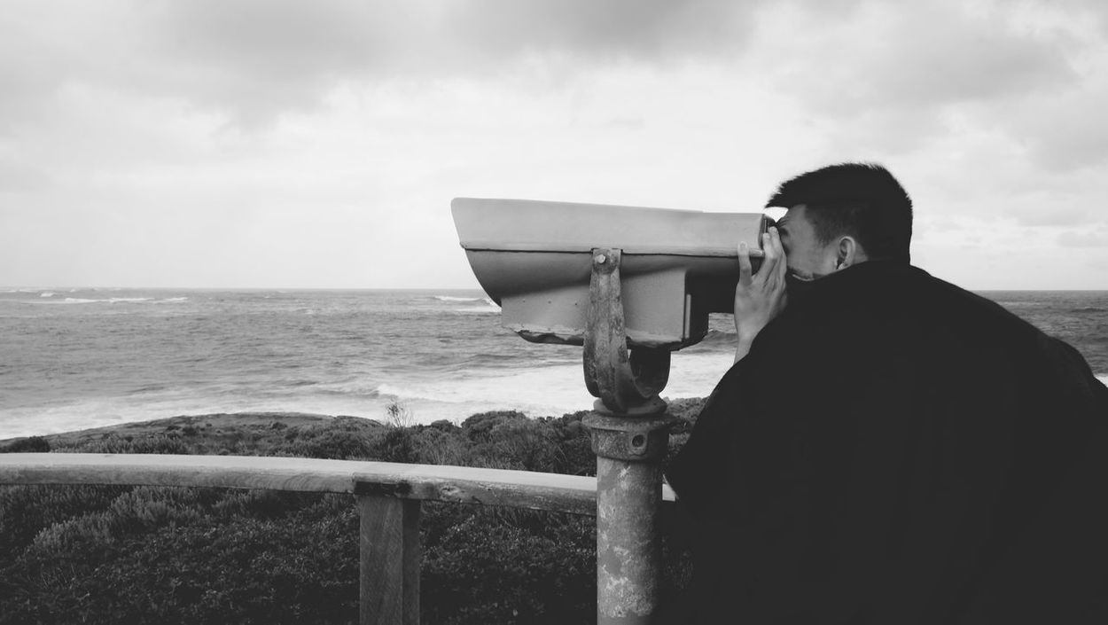 Beach Beauty In Nature Cloud - Sky Day Horizon Over Water Leisure Activity Men Nature One Person Outdoors People Real People Rear View Scenics Sea Sky Standing Telescope Water Young Adult The Great Outdoors - 2017 EyeEm Awards Binoculars Coin Operated Monochrome