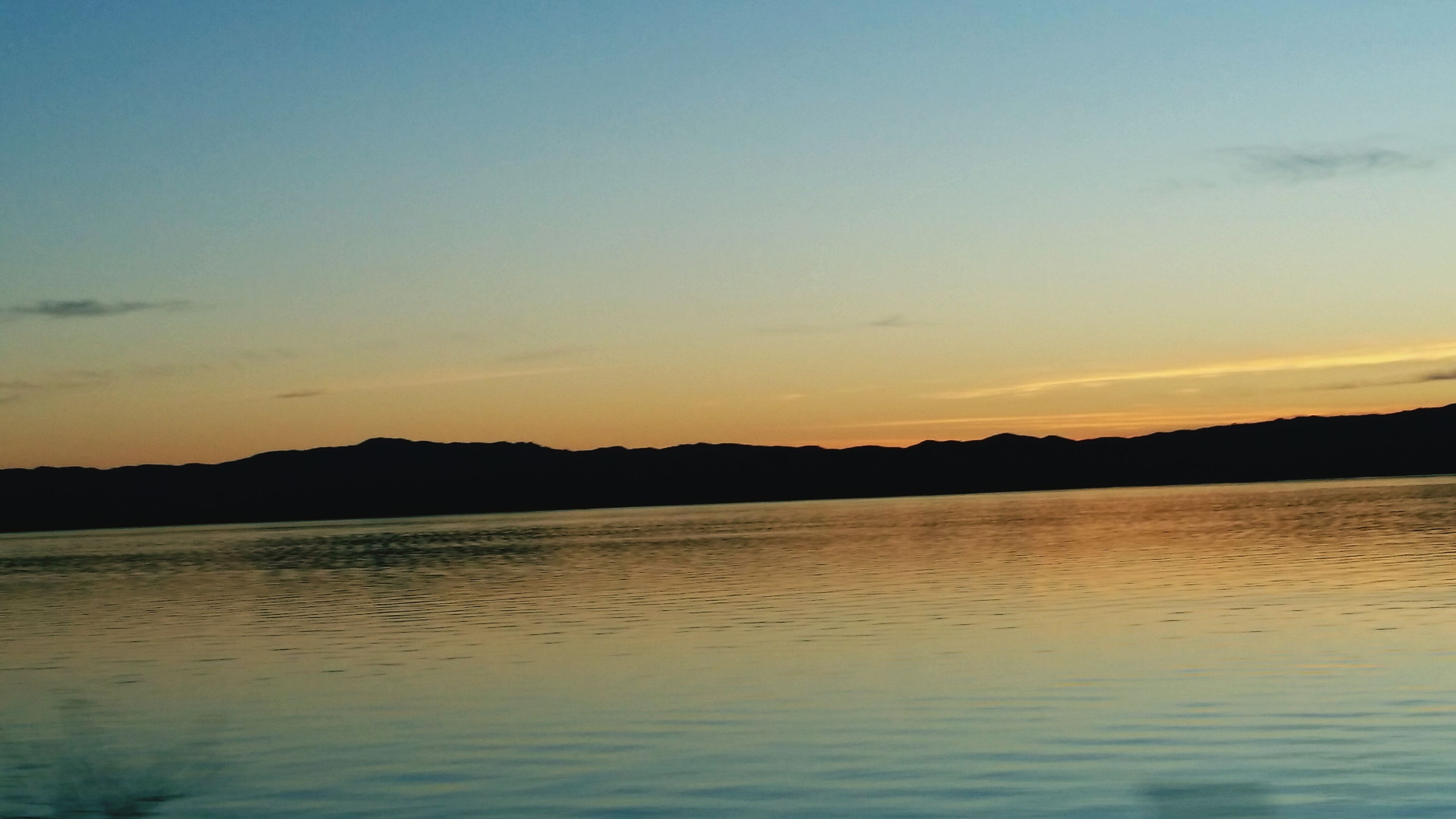 sunset, tranquil scene, water, scenics, tranquility, silhouette, beauty in nature, lake, sky, nature, idyllic, reflection, waterfront, copy space, dusk, orange color, non-urban scene, calm, outdoors, landscape